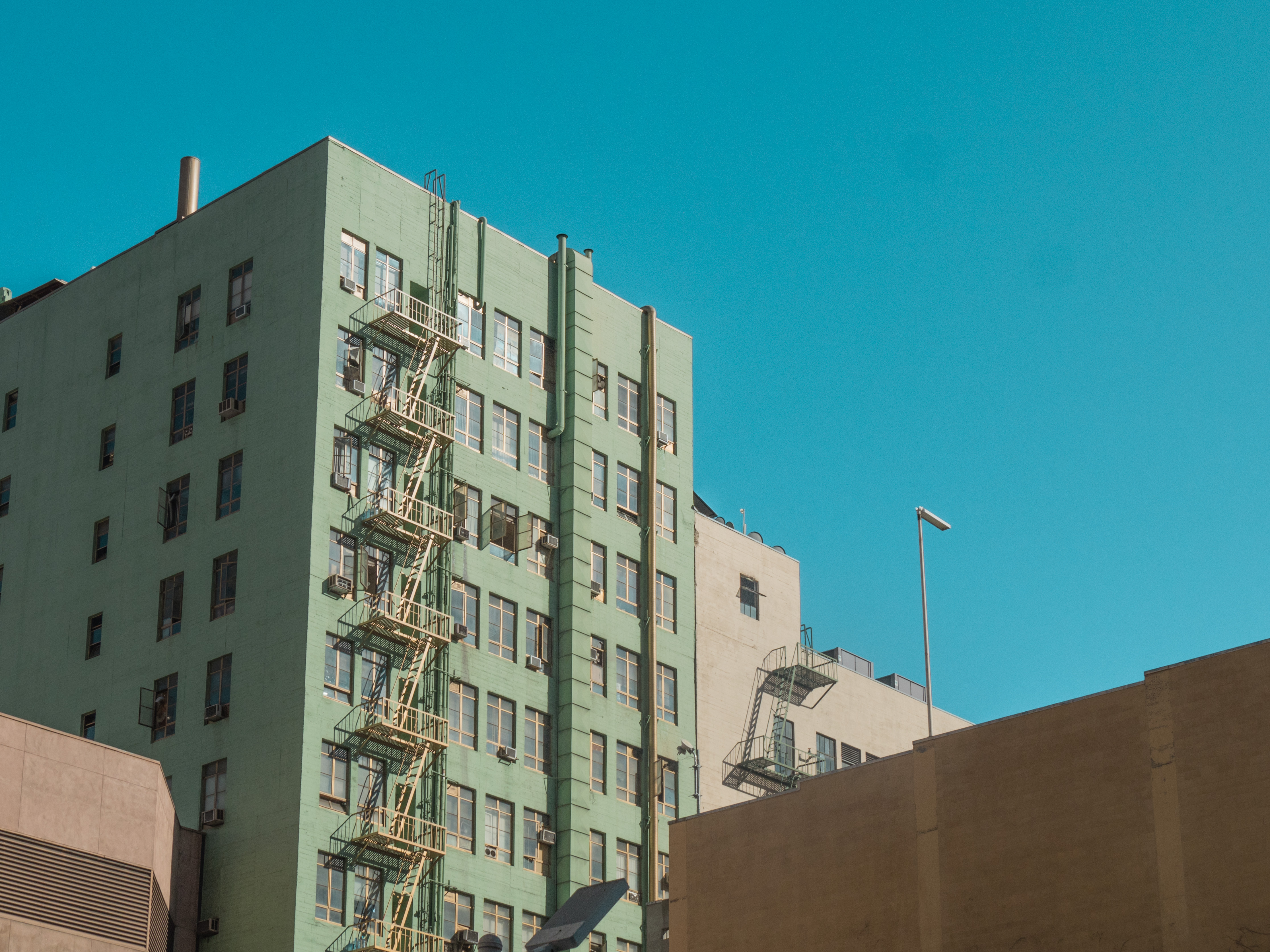 A tall turquoise building with a fire escape sandwiched next to a tan stucco building against a blue sky.