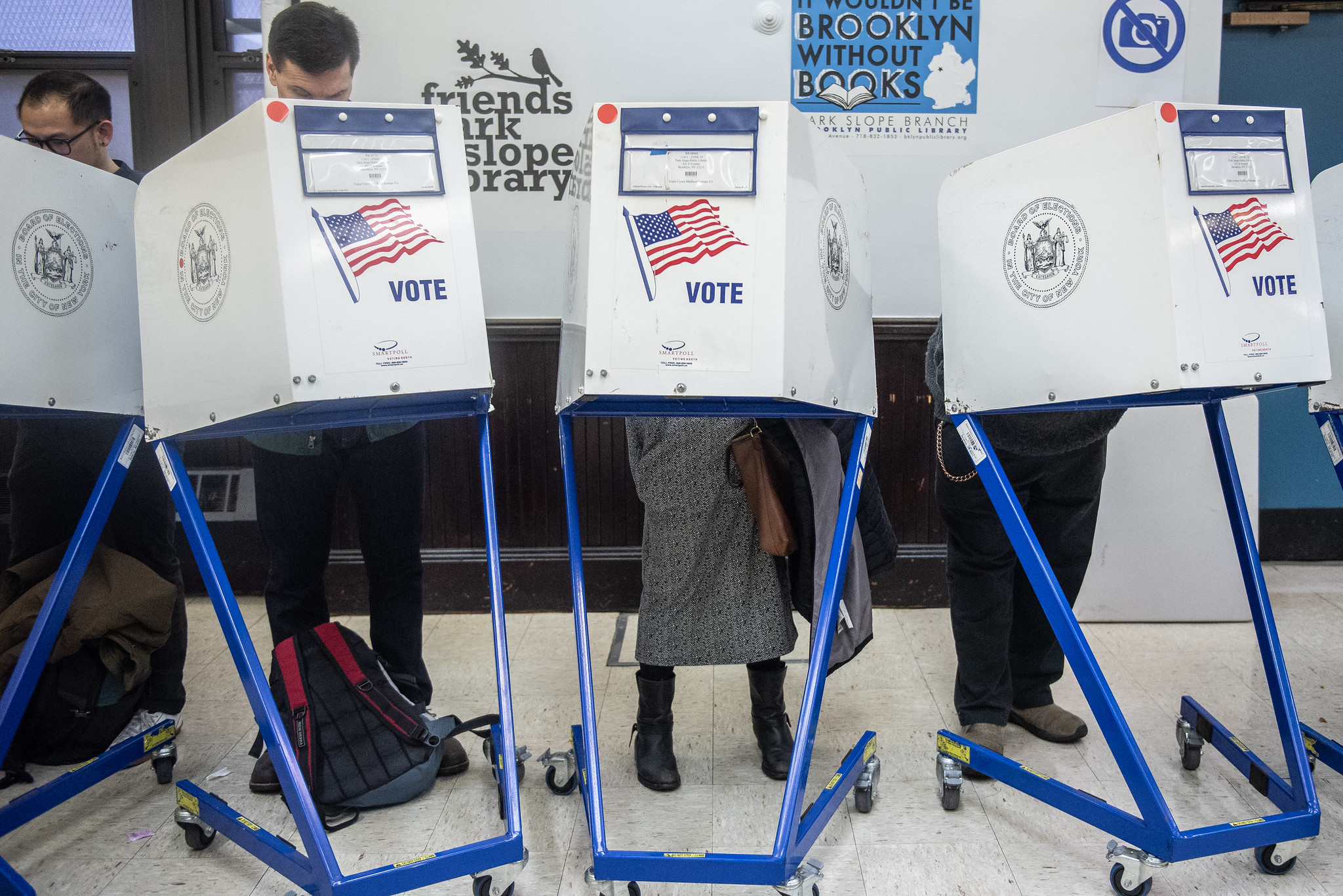 Three voters stand at the polls casting their votes in 2018's general election.