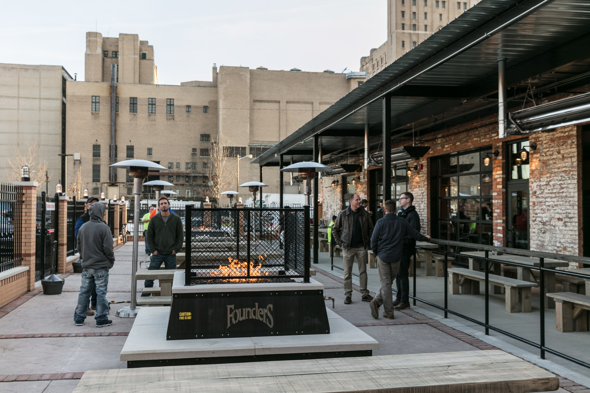 Customers mill around a lit fire pit on the patio at Founders in Detroit.