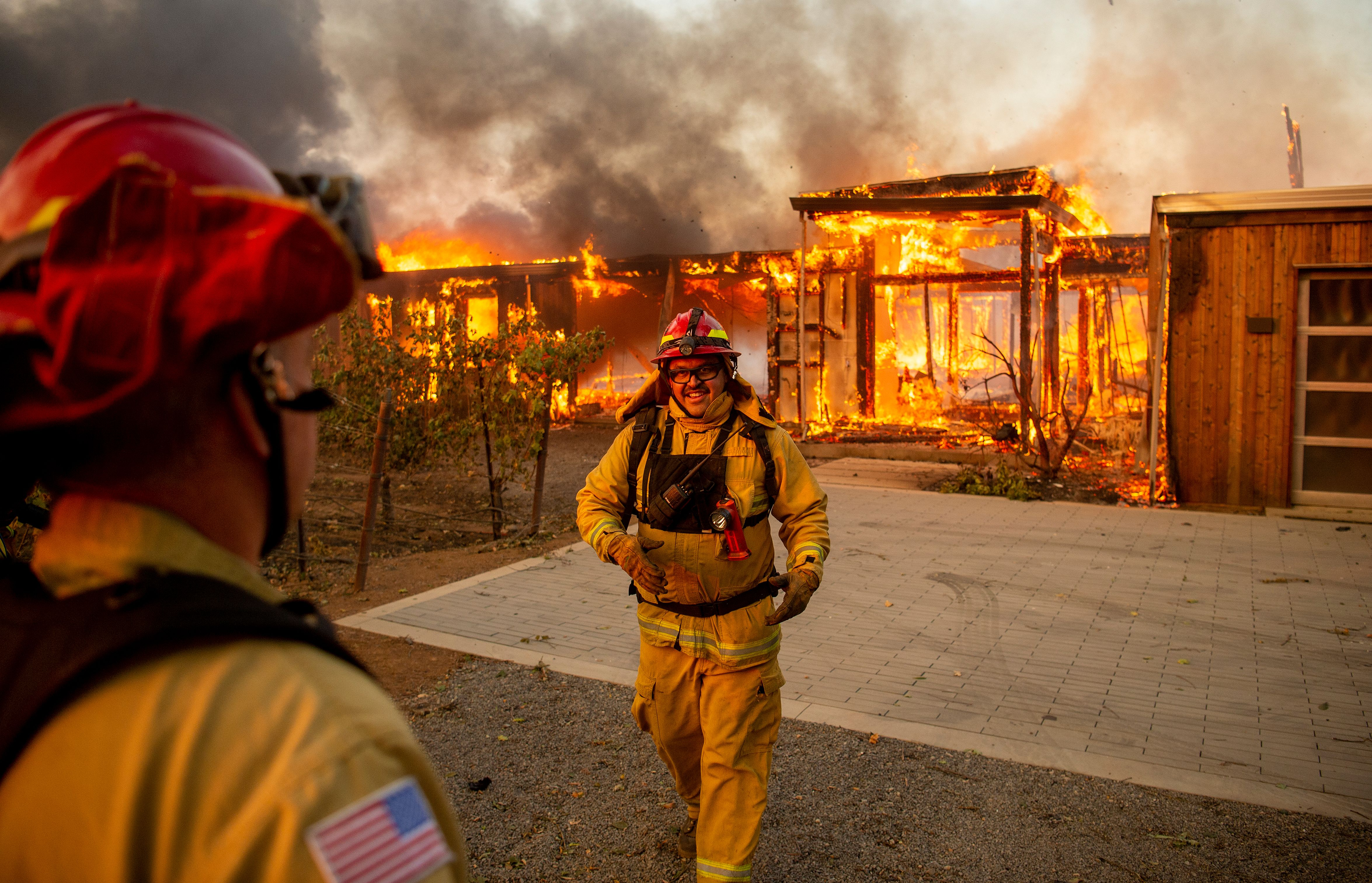 A house on fire with two firefighters battling it.