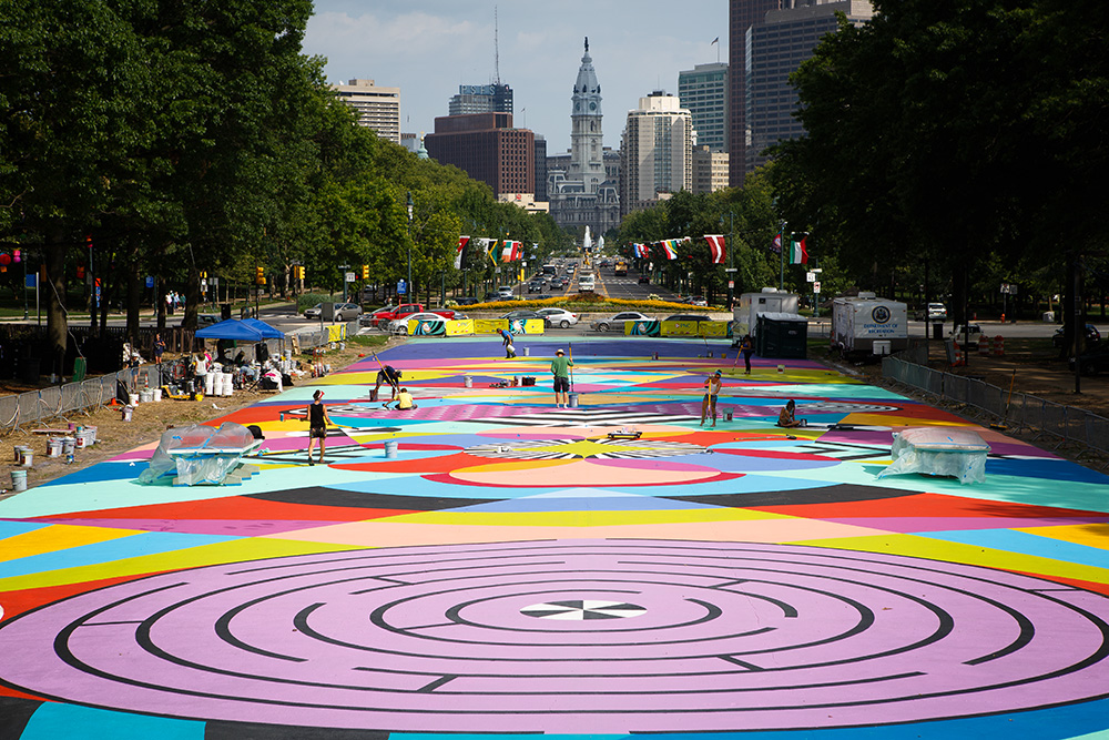 A colorful graphic mural is being painted in the street by people using giant brushes with the skyline of Philadelphia in the background.