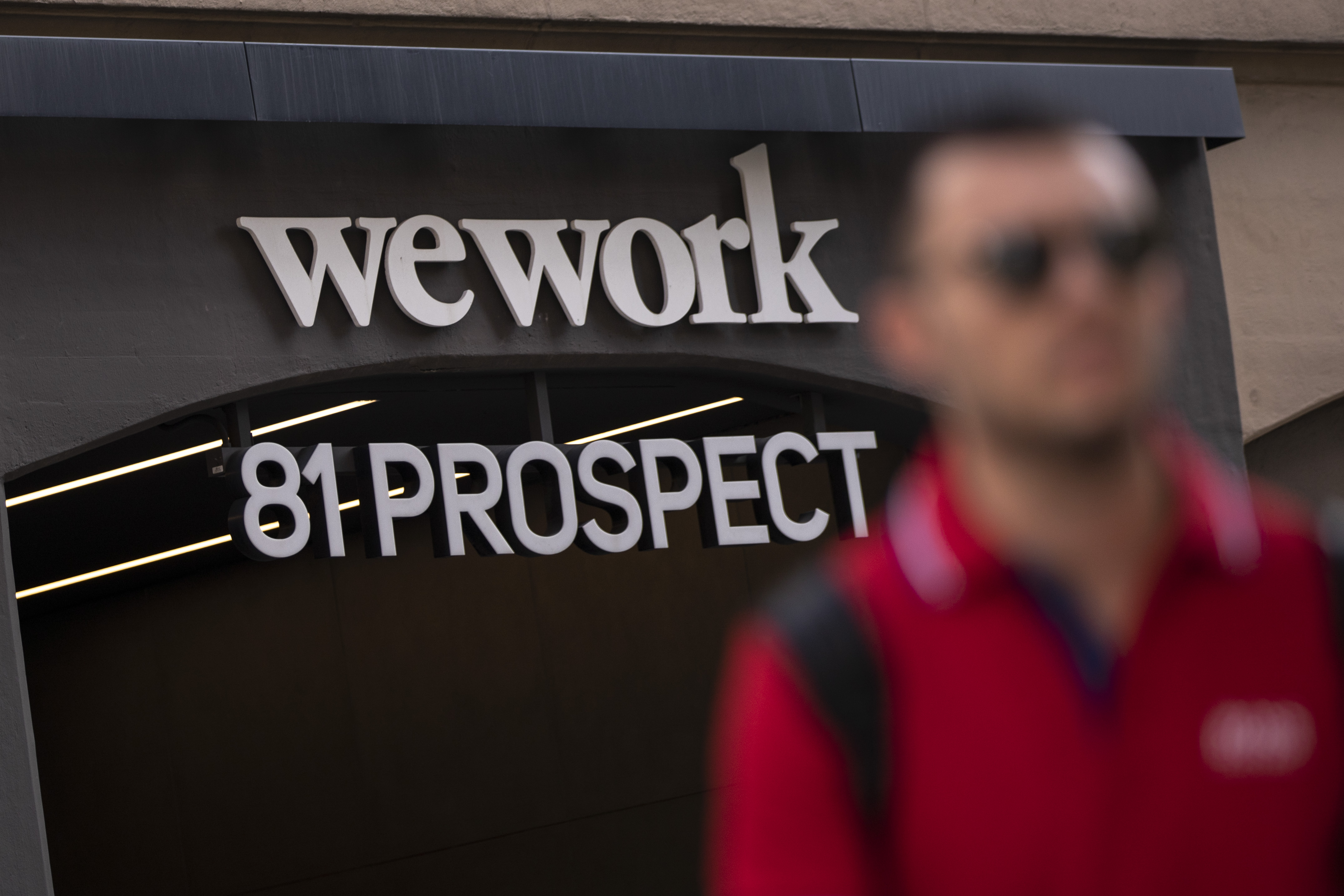 Man whose face is out of focus walks away from a WeWork location at 81 Prospect in New York City.