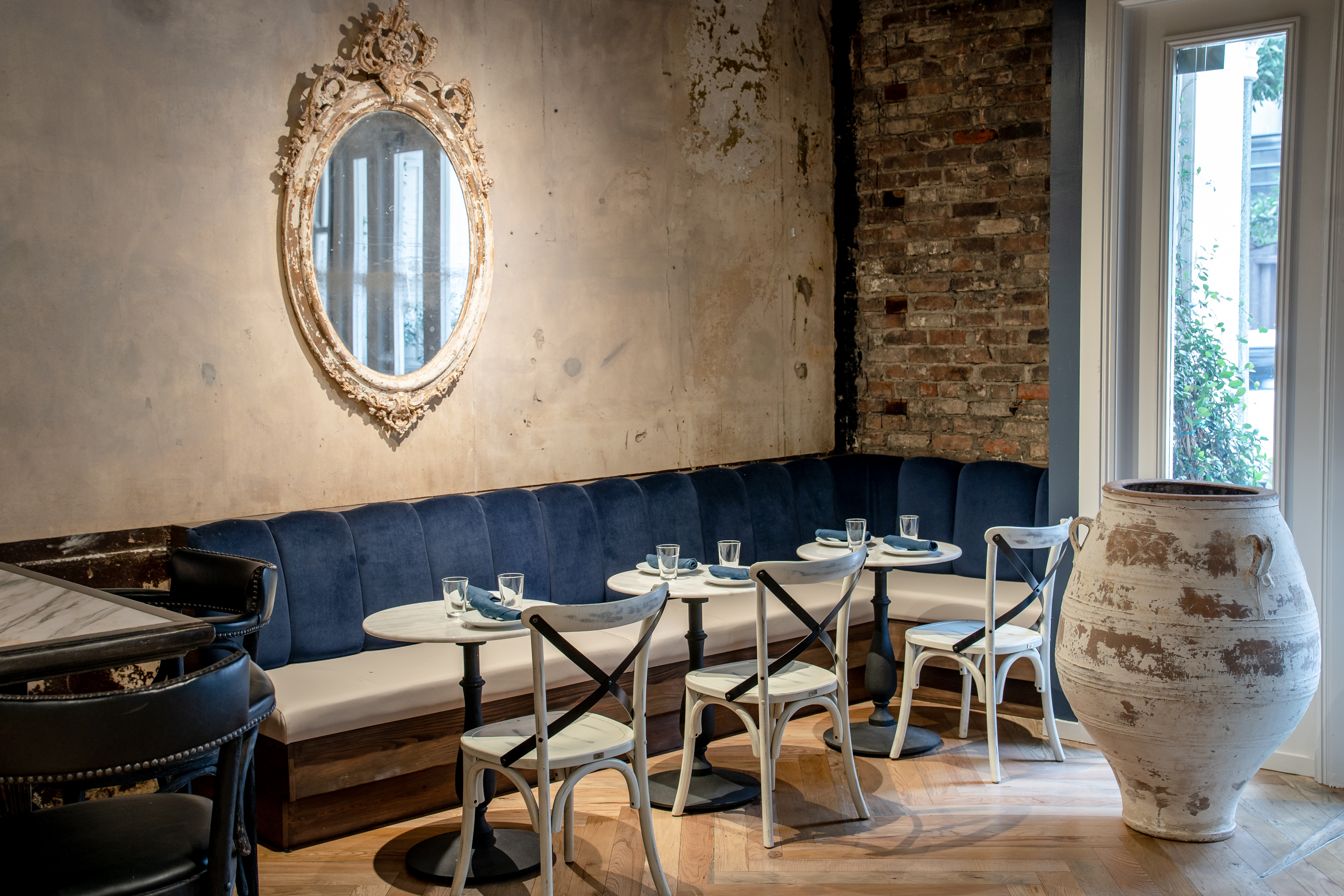 The interior of a restaurant with an oval mirror hanging on a wall, blue velvet bench seating, an small exposed brick wall and a large olive pot