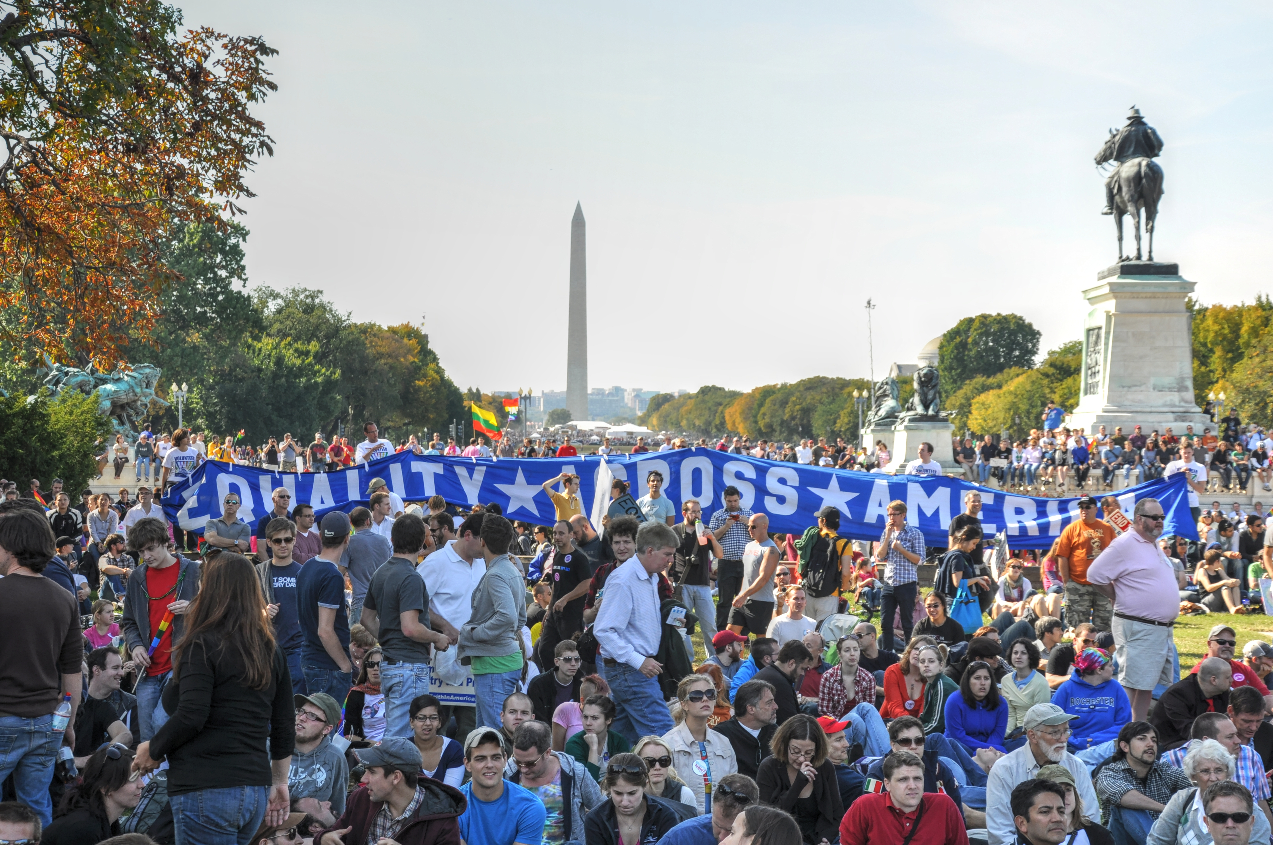 A group of protesters sitting and holding a banner on a large open space. A tall obelisk and a statue of a man on a horse are in the background.