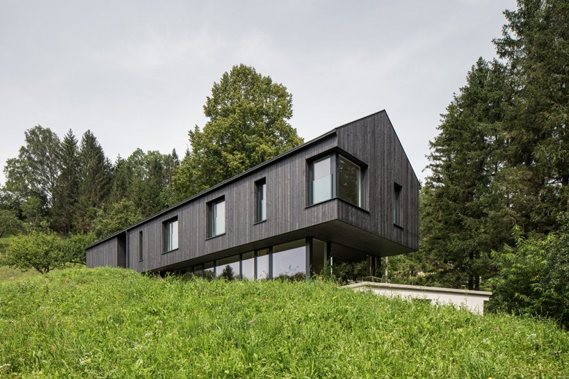 A black gable-roofed house sits on a grassy plot of land. The top level cantilevers over the glassy lower level.
