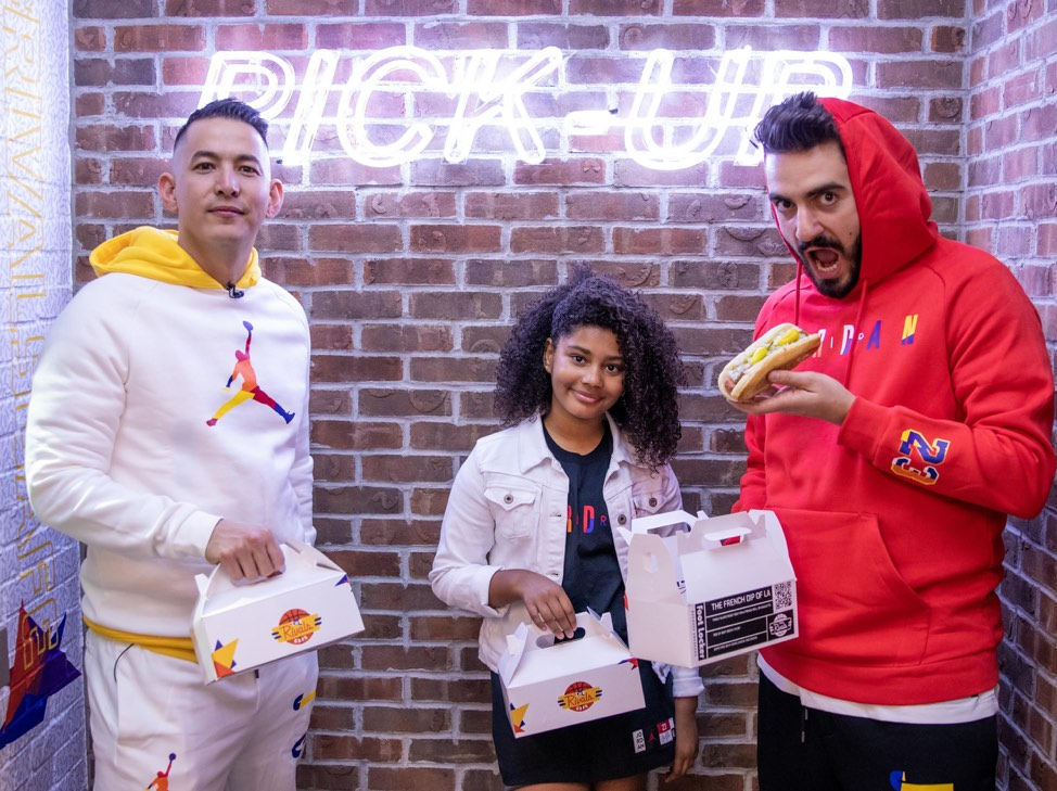 Several people in Nike gear hold food inside of a Foot Locker store.