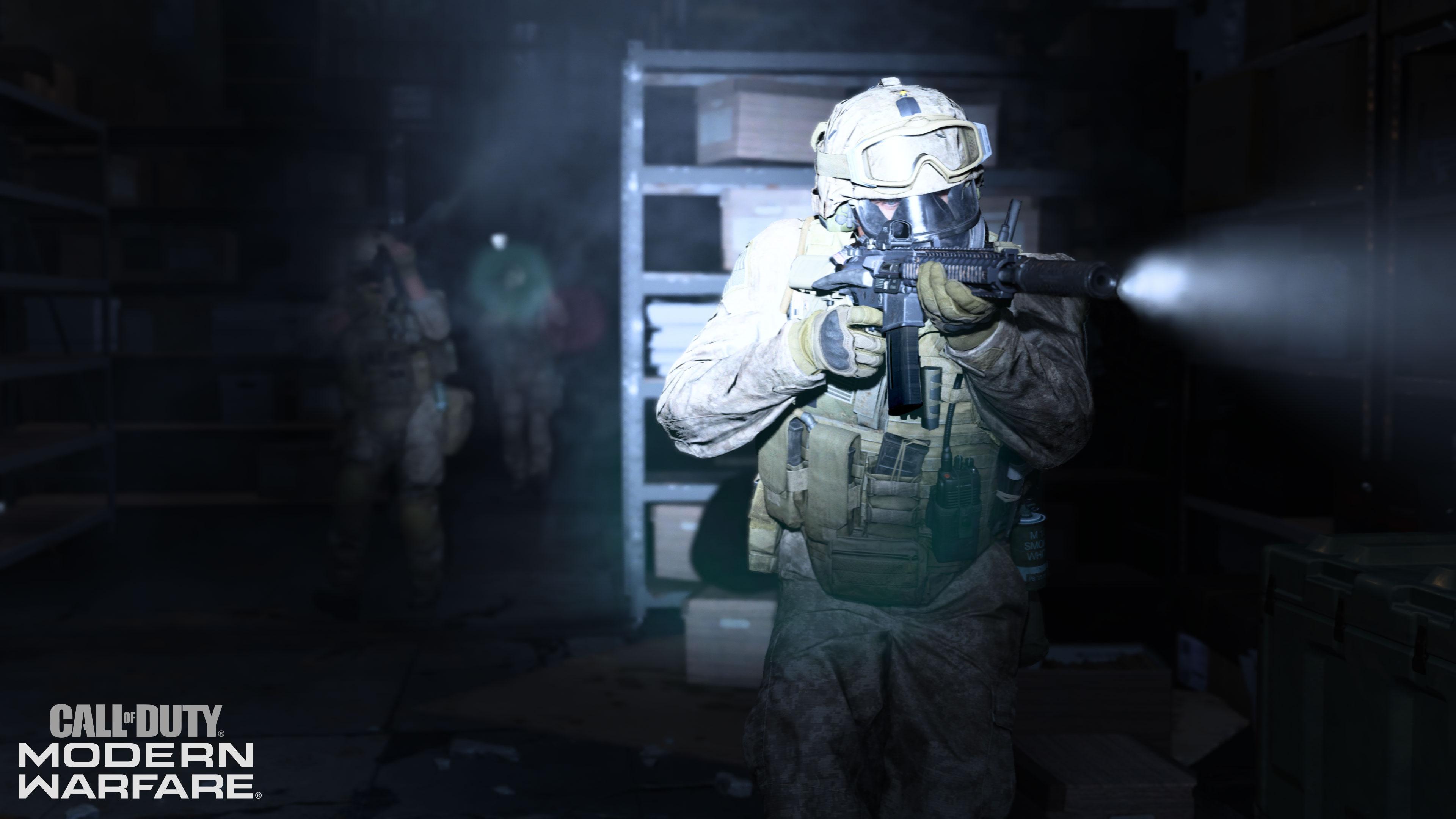 A soldier moves through a dark room, a flashlight attached to his gun