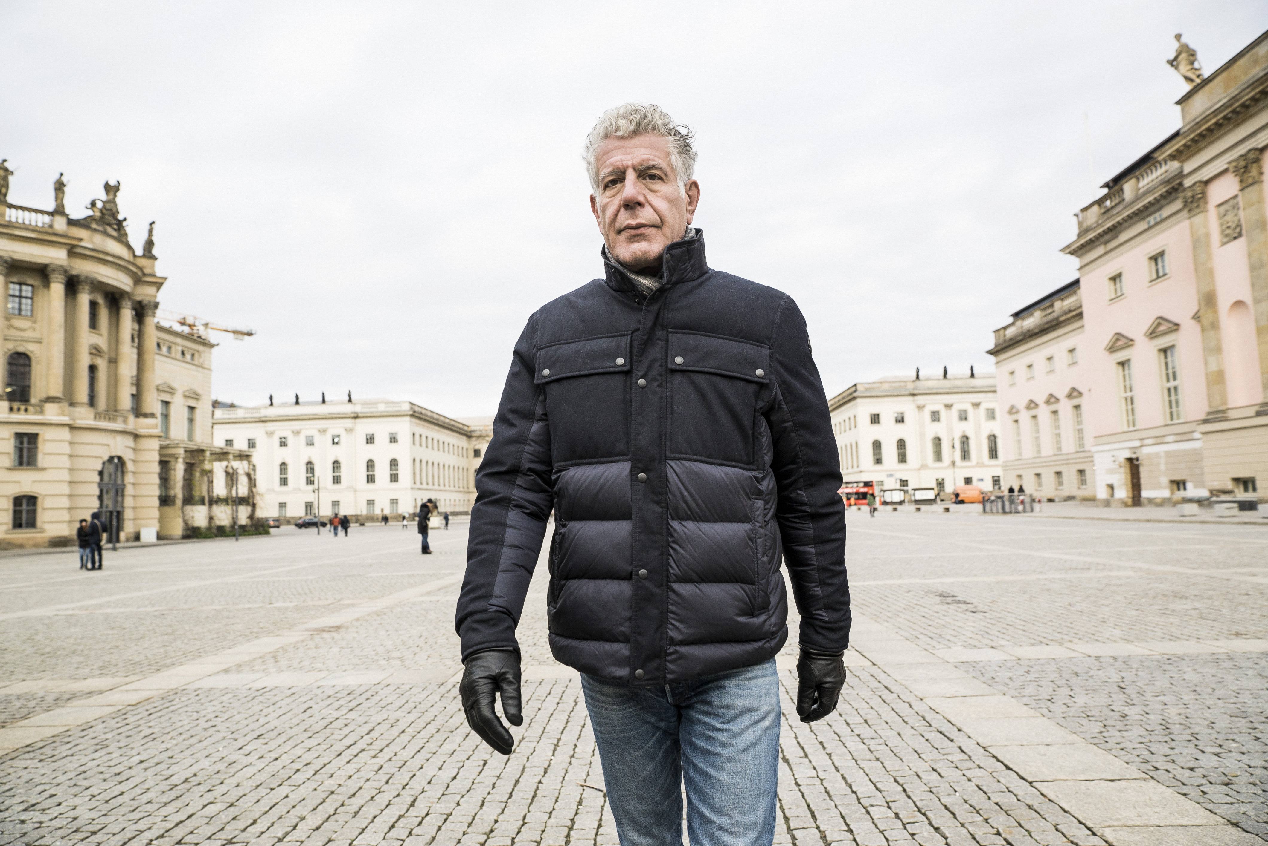 Anthony Bourdain strides forward in an outdoor plaza.