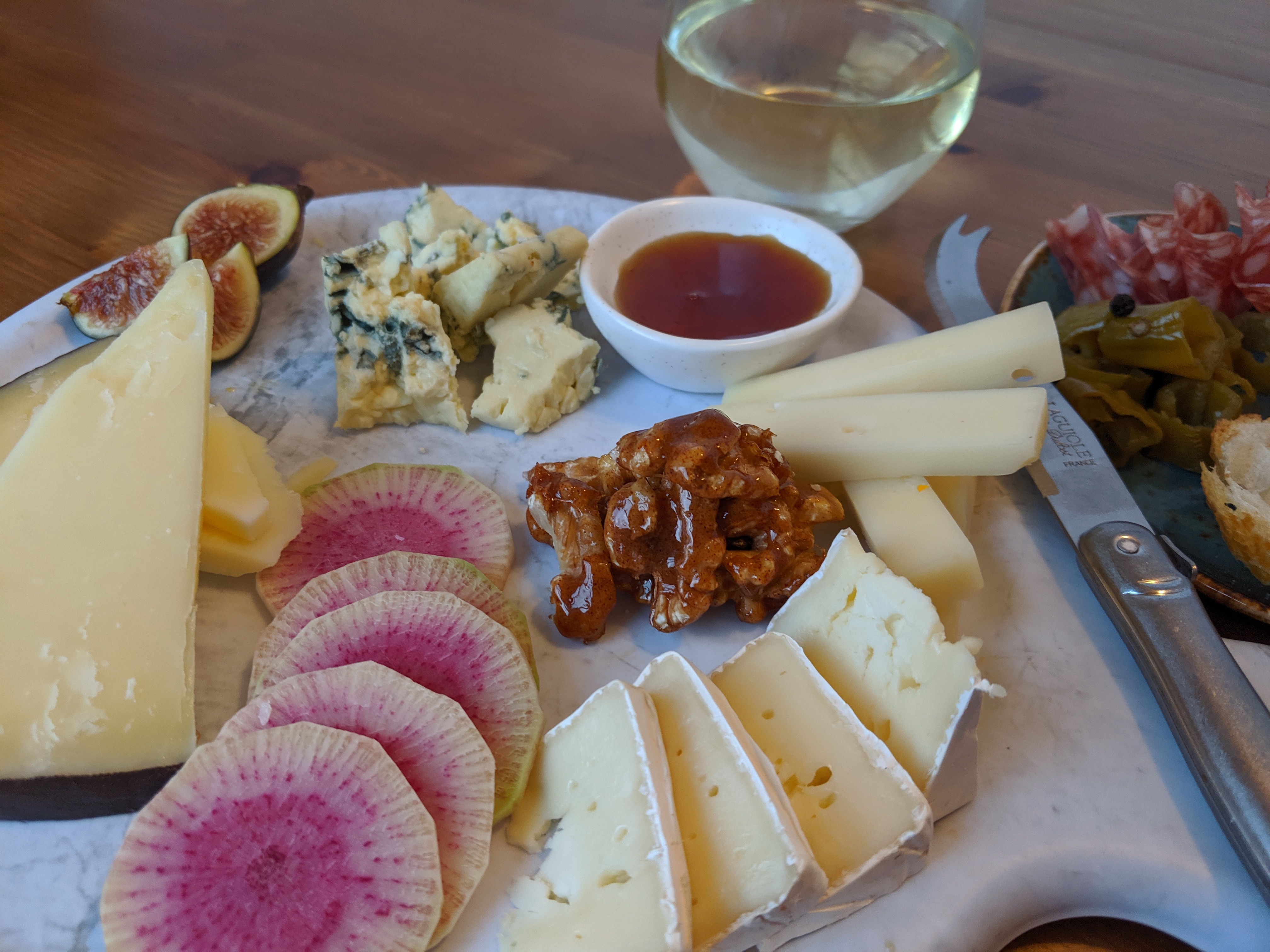 A cheese plate with piles of different kinds of cheeses, slices of watermelon radish, nut brittle, and more.