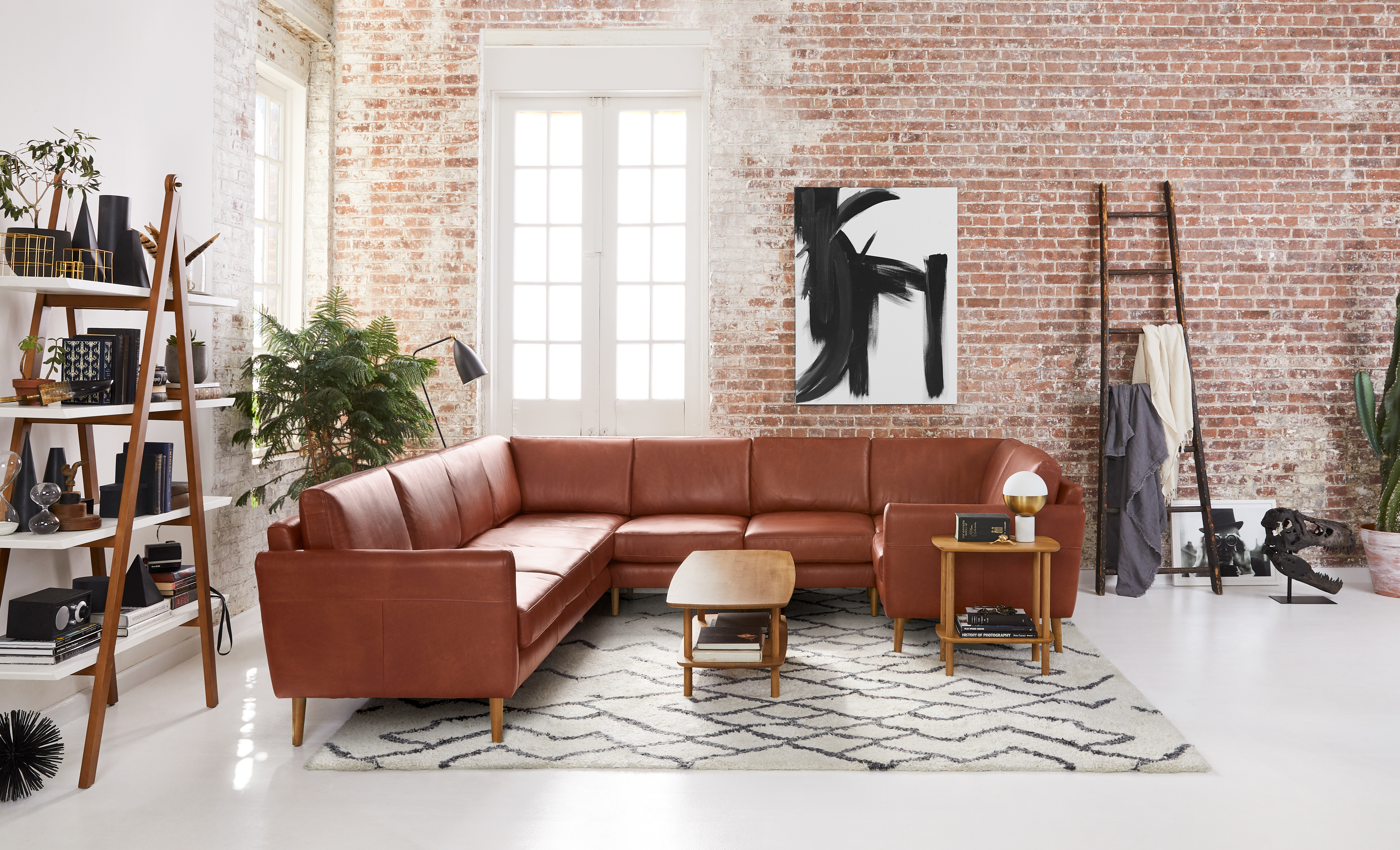 Brown leather sectional in brick-walled living room.