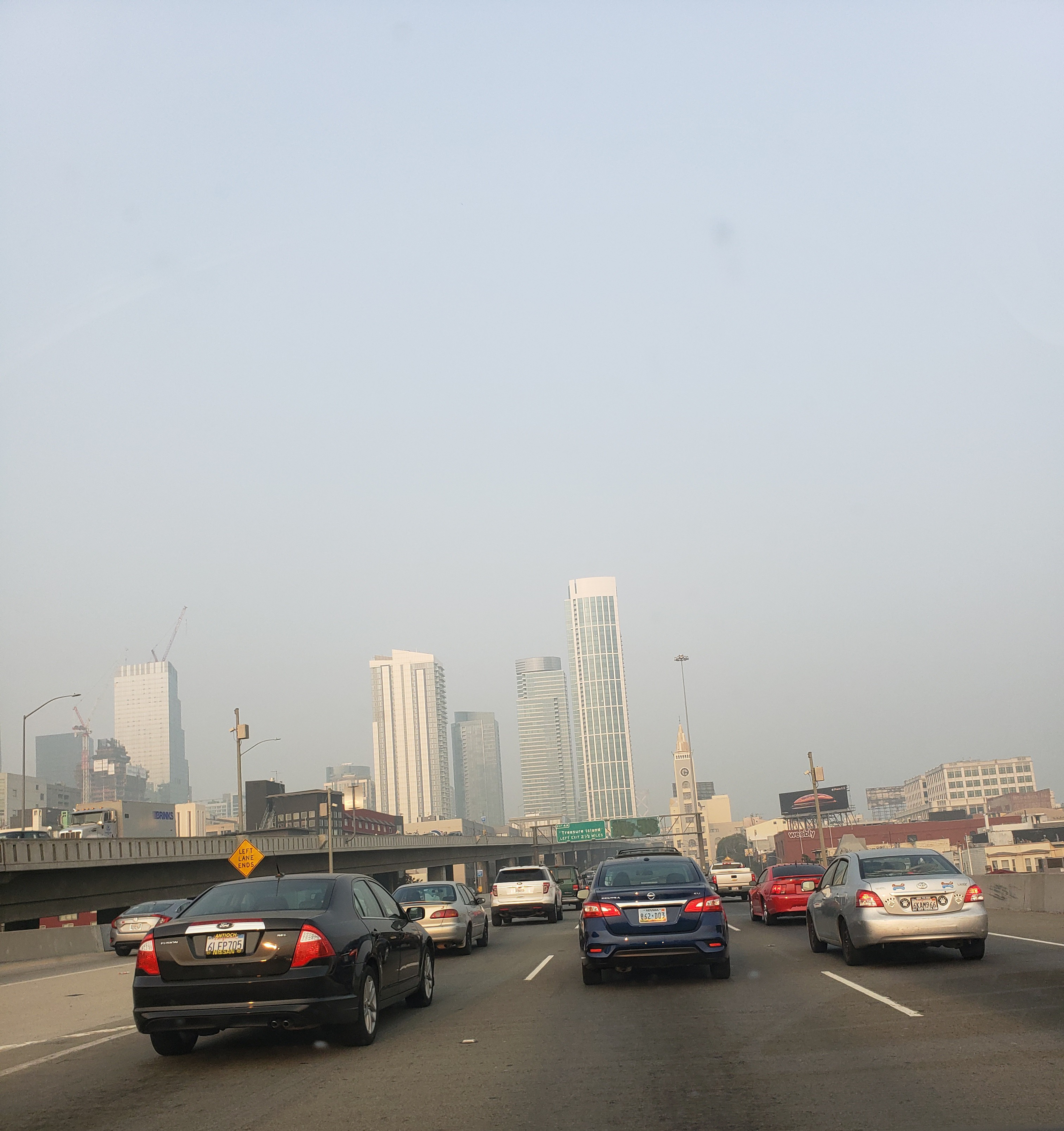Gray smoke hovering over a series of high-rise buildings, with cars on the freeway below.