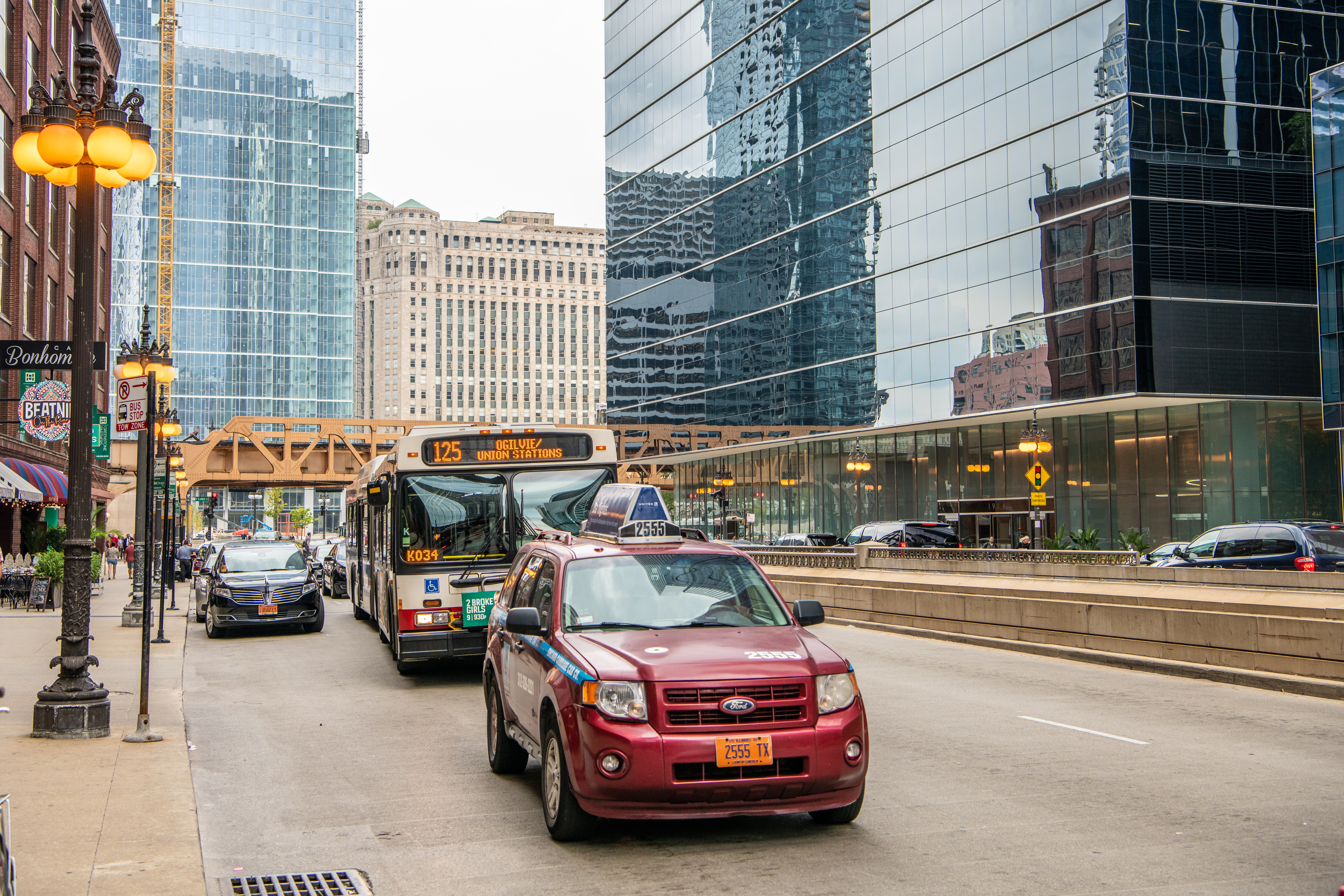 A bus and a car on a downtown street in Chicago.
