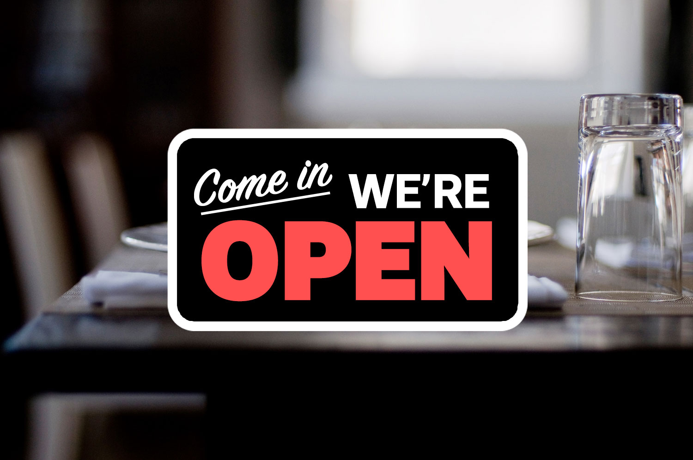 "A ""come on in we're open"" sign logo over a nondescript restaurant stock photo."