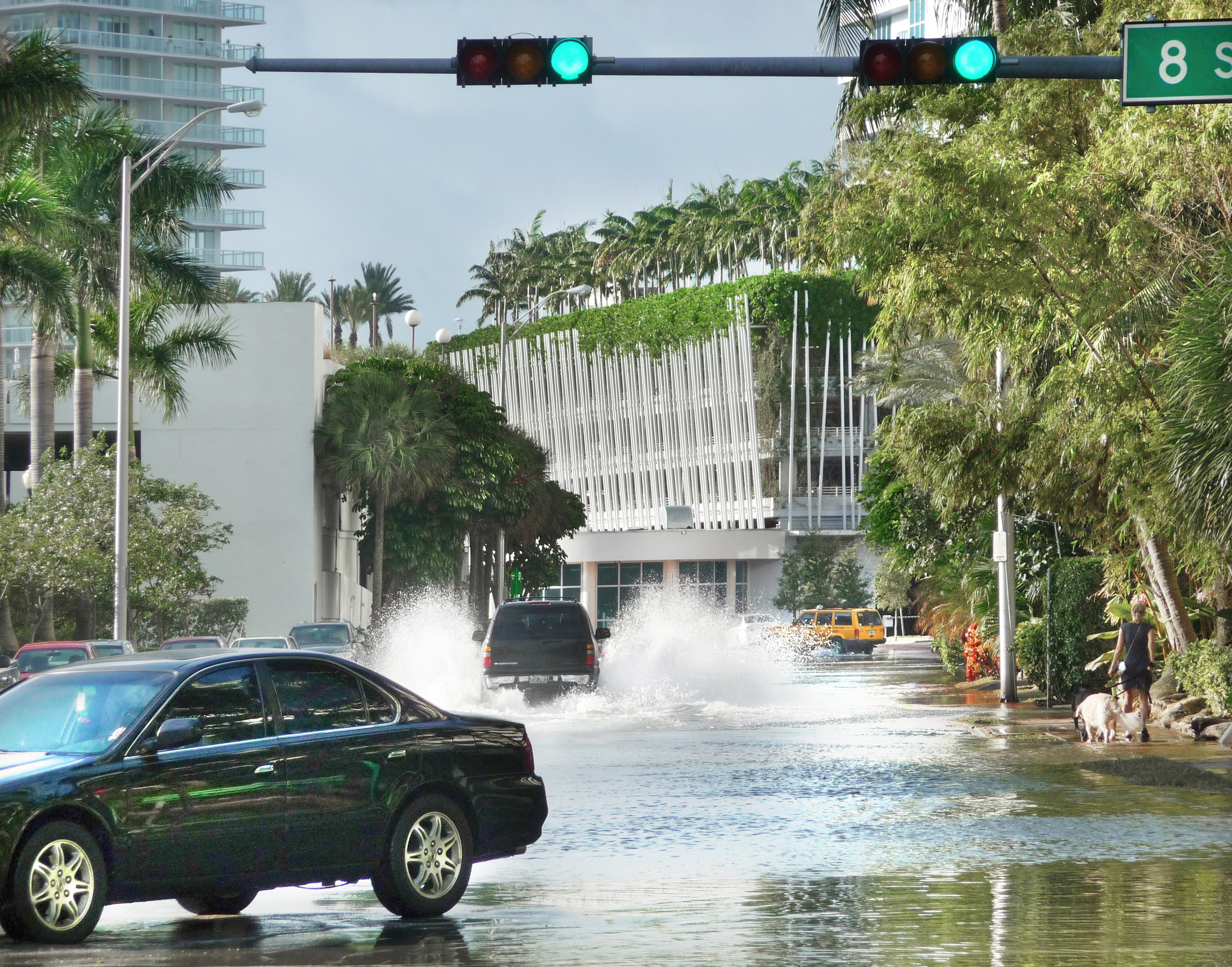 Cars speeding through an intersection flooded with water during a high tide.
