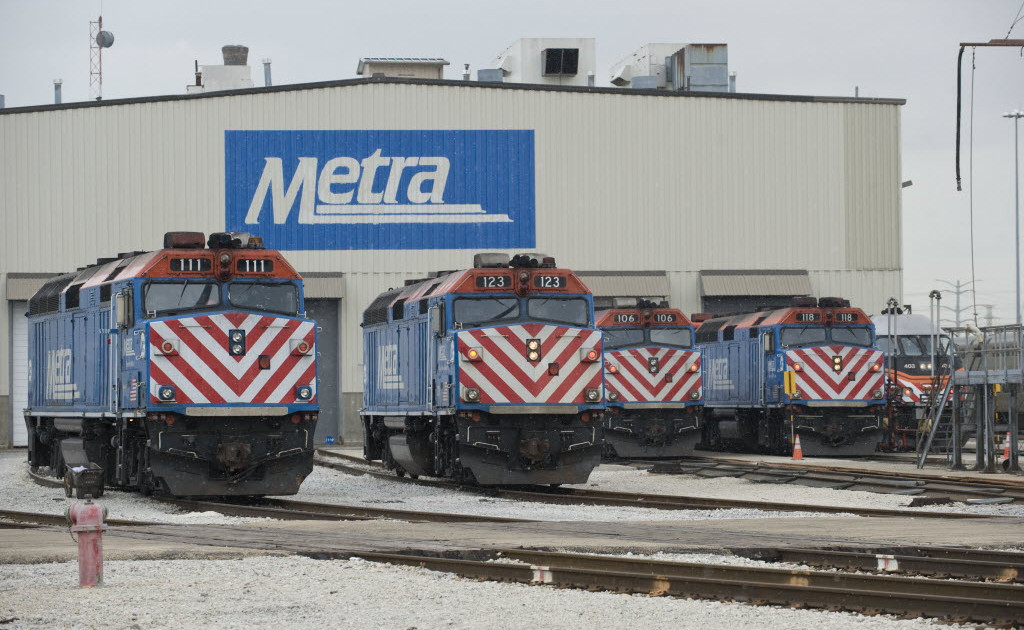 Metra trains outside a train barn.