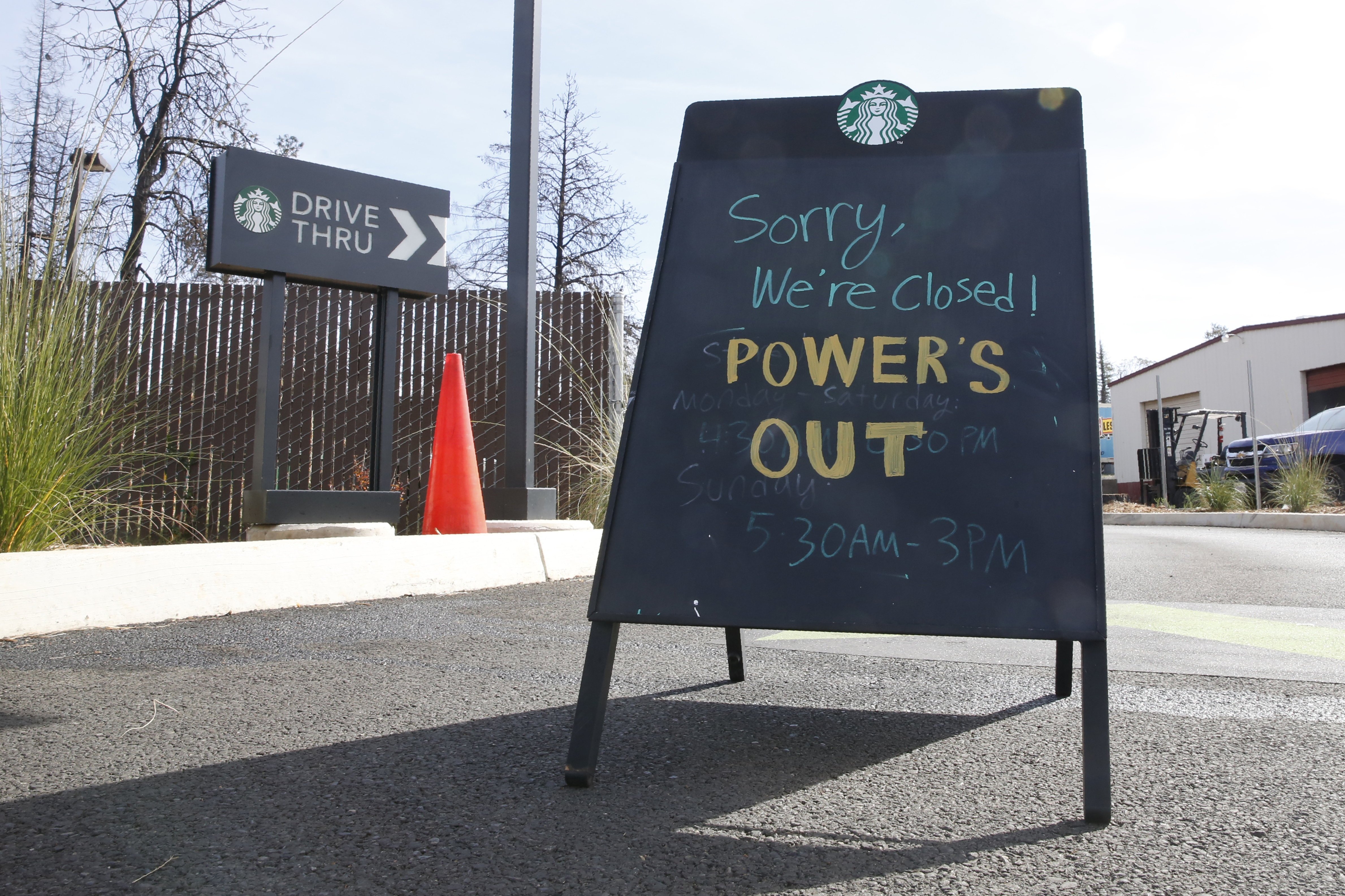 """A sign saying """"Sorry, we're closed. Power is out."""" at a Starbucks."""
