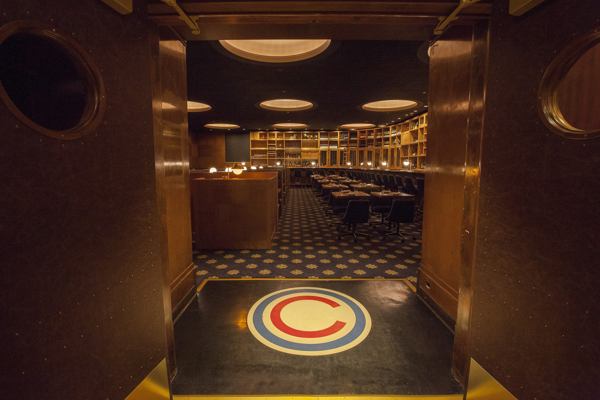 The entrance to Cherry Circle Room inside the Chicago Athletic Association hotel has plenty of historic wood paneling, wooden furniture, drim lighting, and the logo on the floor.