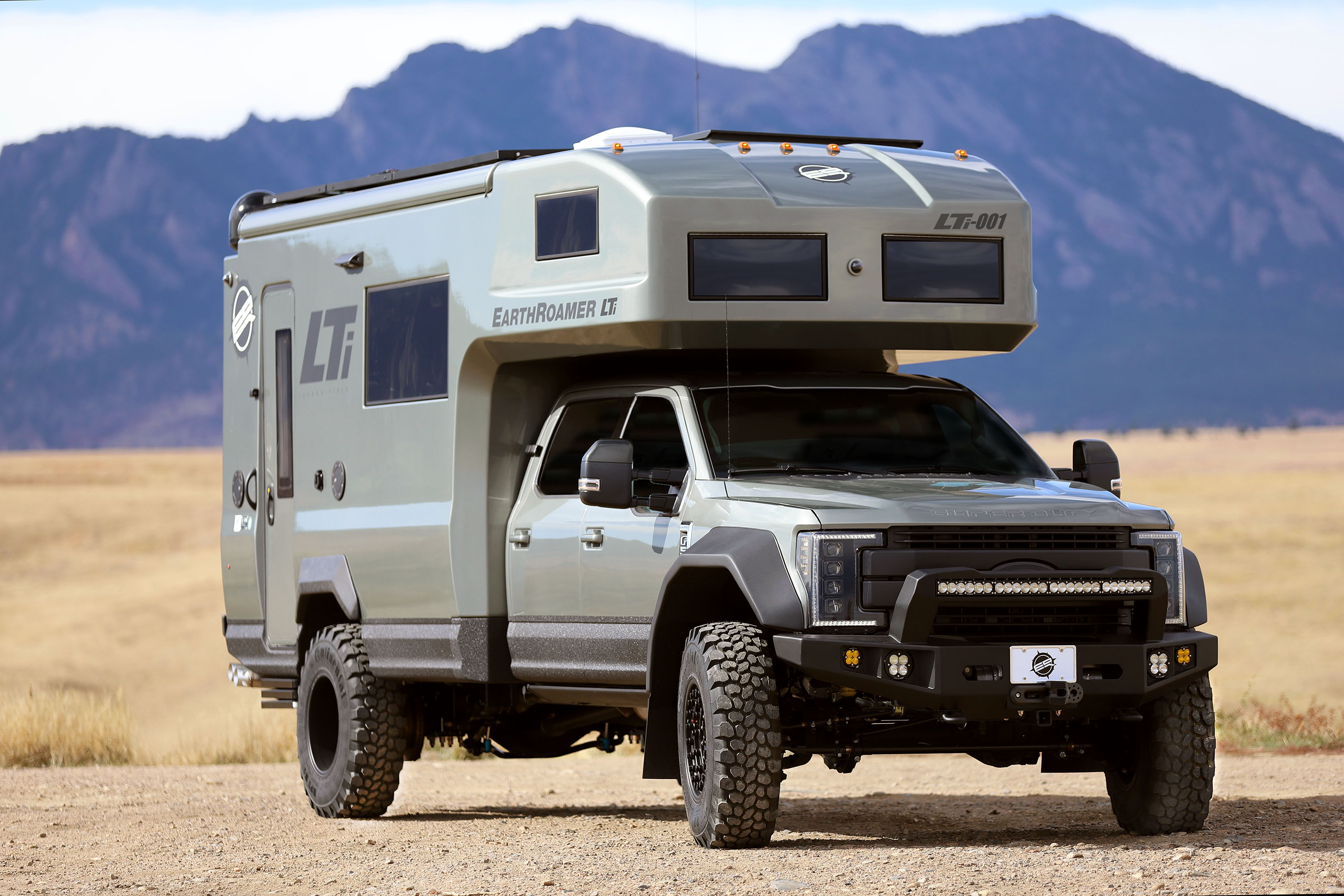 An exterior view of a silver four-wheel-drive camper with an over-the-cab sleeping area, big burly tires, and mountains in the background.