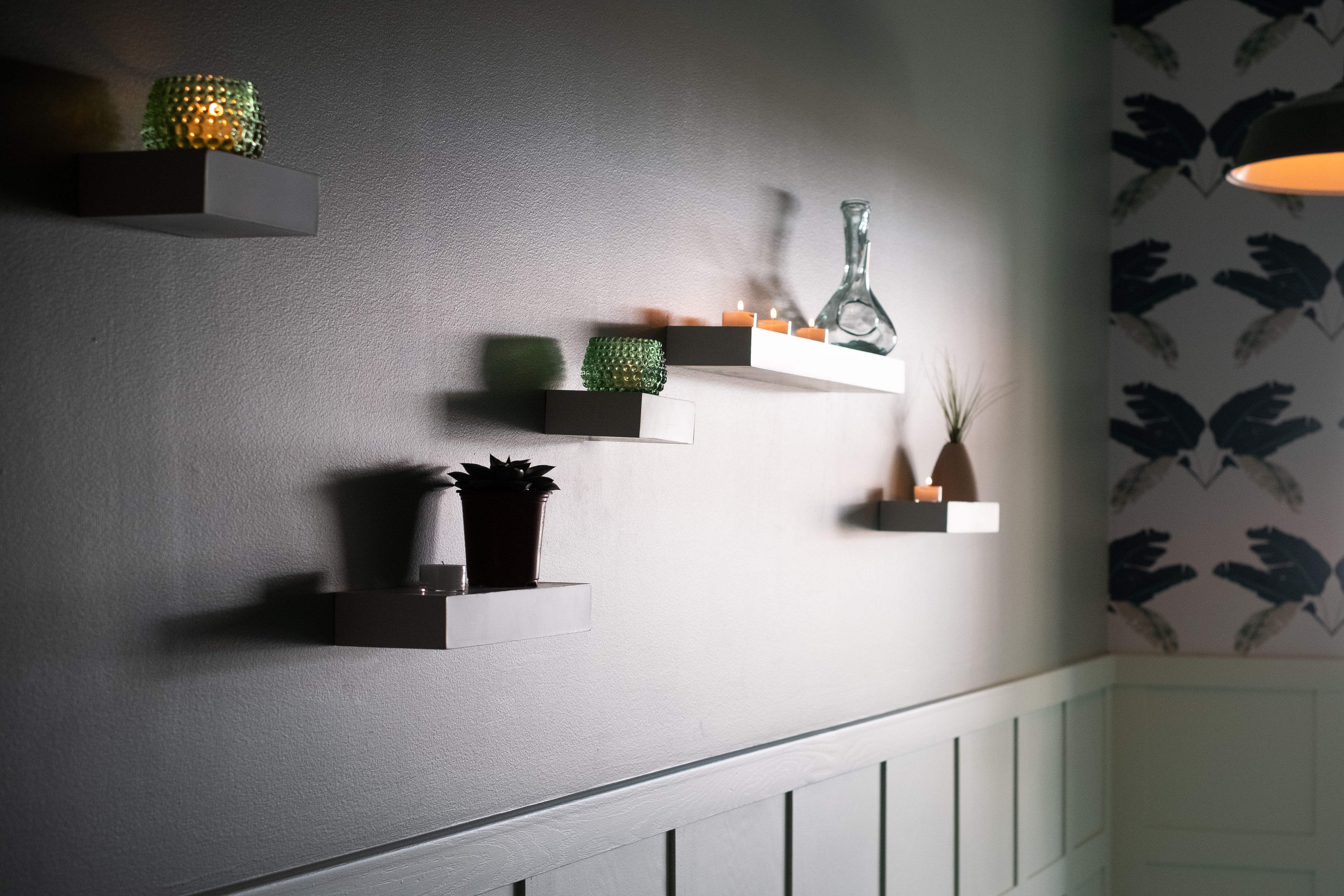 A wall with sconces illuminated by a ray of natural light