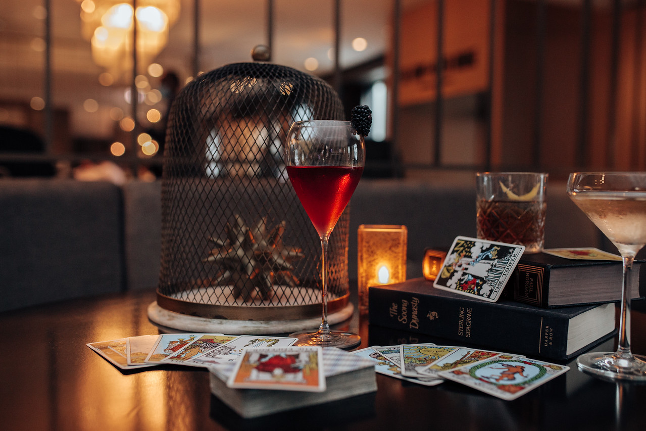 A red cocktail in a long-stemmed glass stands on a dark table beside piles of tarot cards.