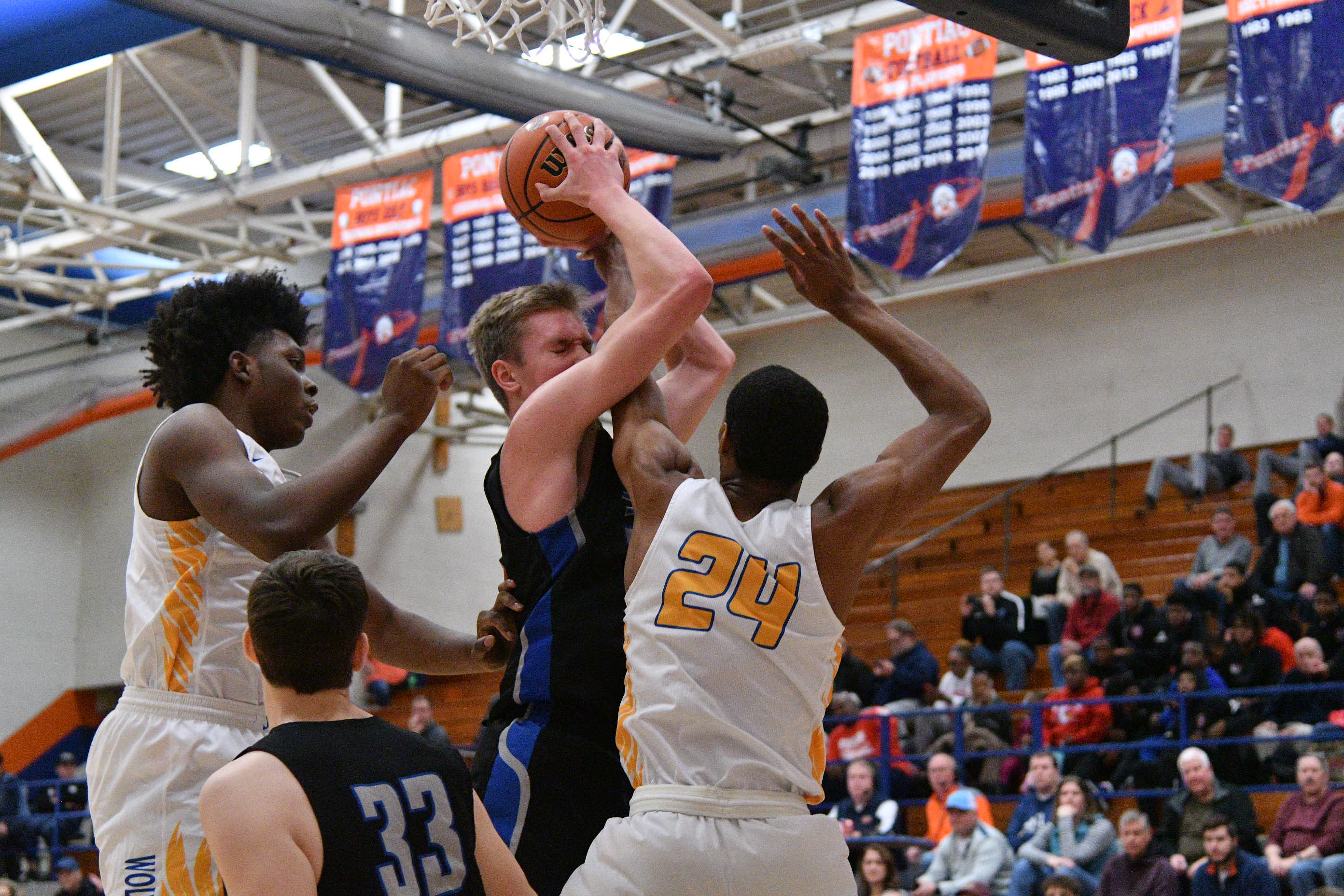 St. Charles North's Connor Linke (34) is hit in the face by Simeon's Jaylen Granger (24) while going for a rebound.