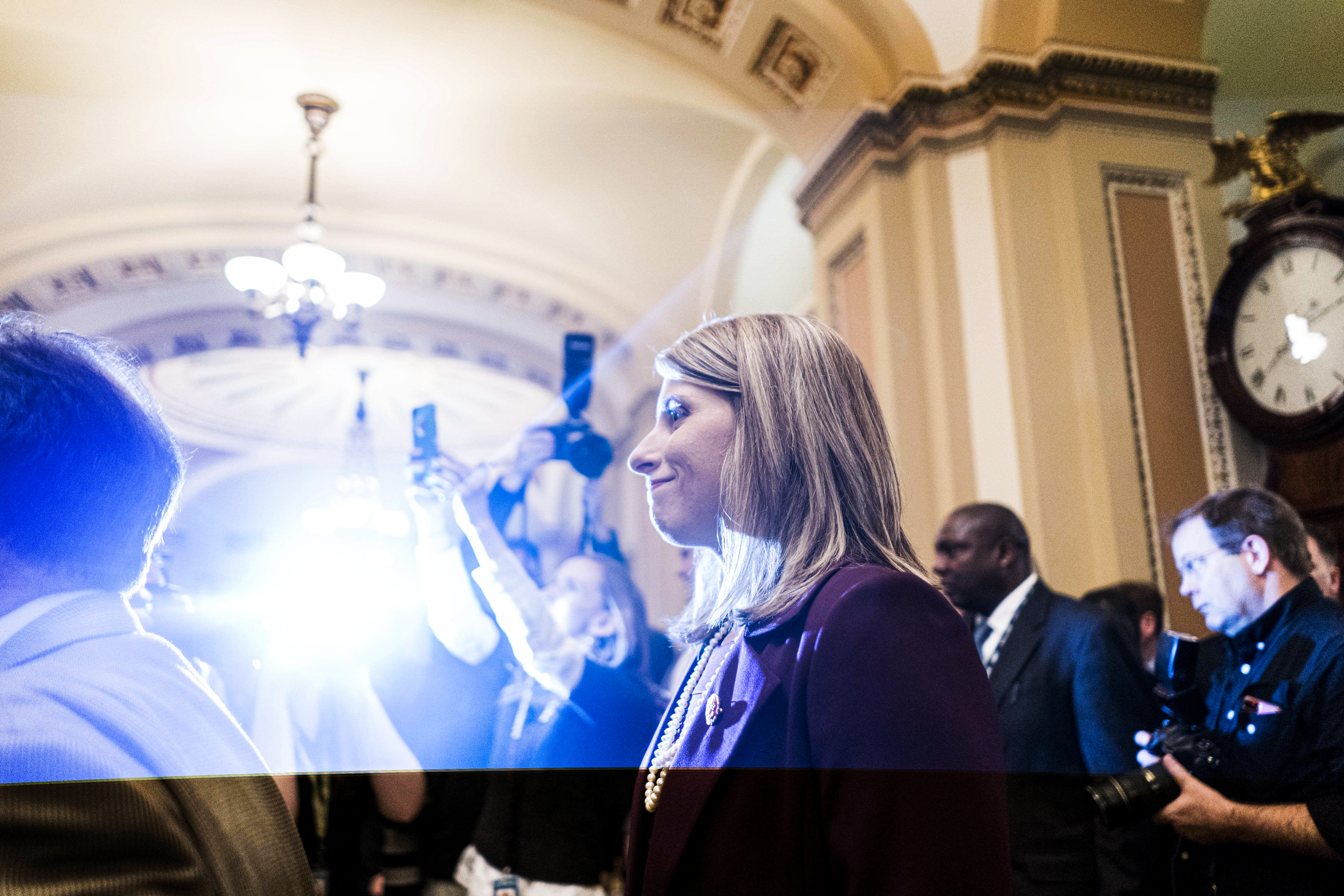Representative Katie Hill surrounded by bright lights and members of the press.