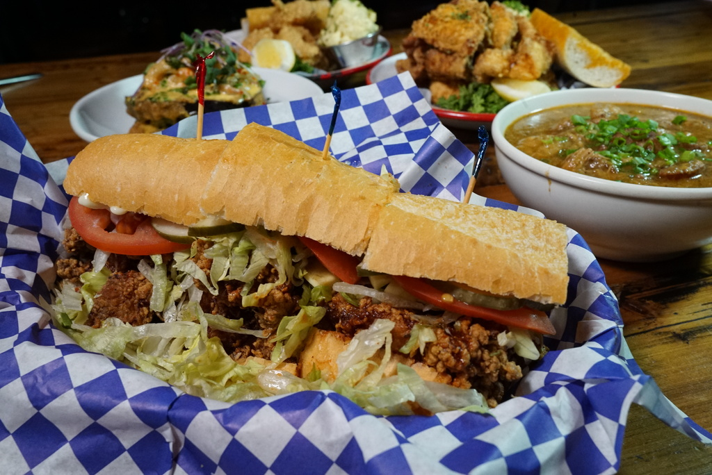 Fried chicken po' boy, served at Ina Mae Tavern, is topped withlettuce, tomato, pickles, mayonnaise and hot sauce.
