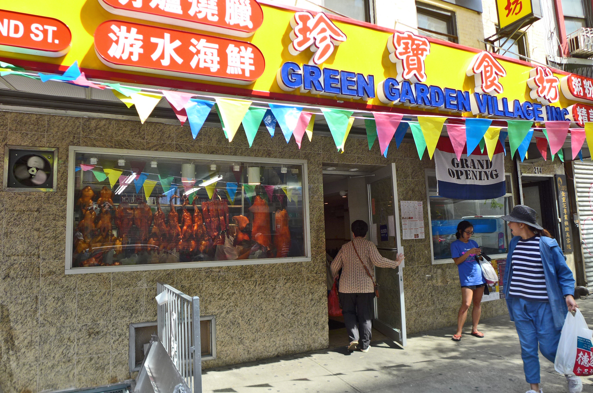 A Chinese restaurant with a red and yellow marquee, pennants shooting from the front...