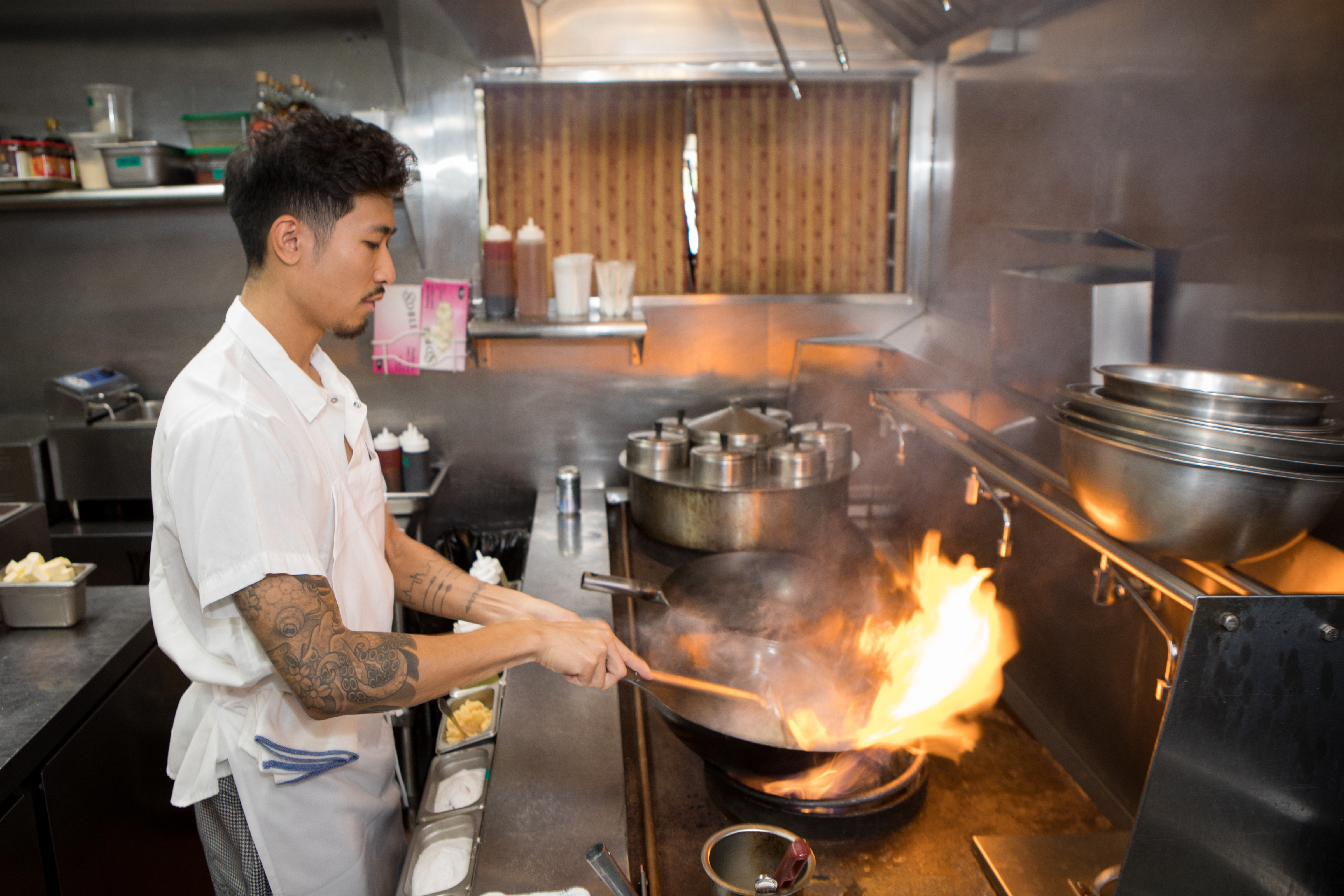 Calvin Eng stirs a flaming wok in the Win Son kitchen,