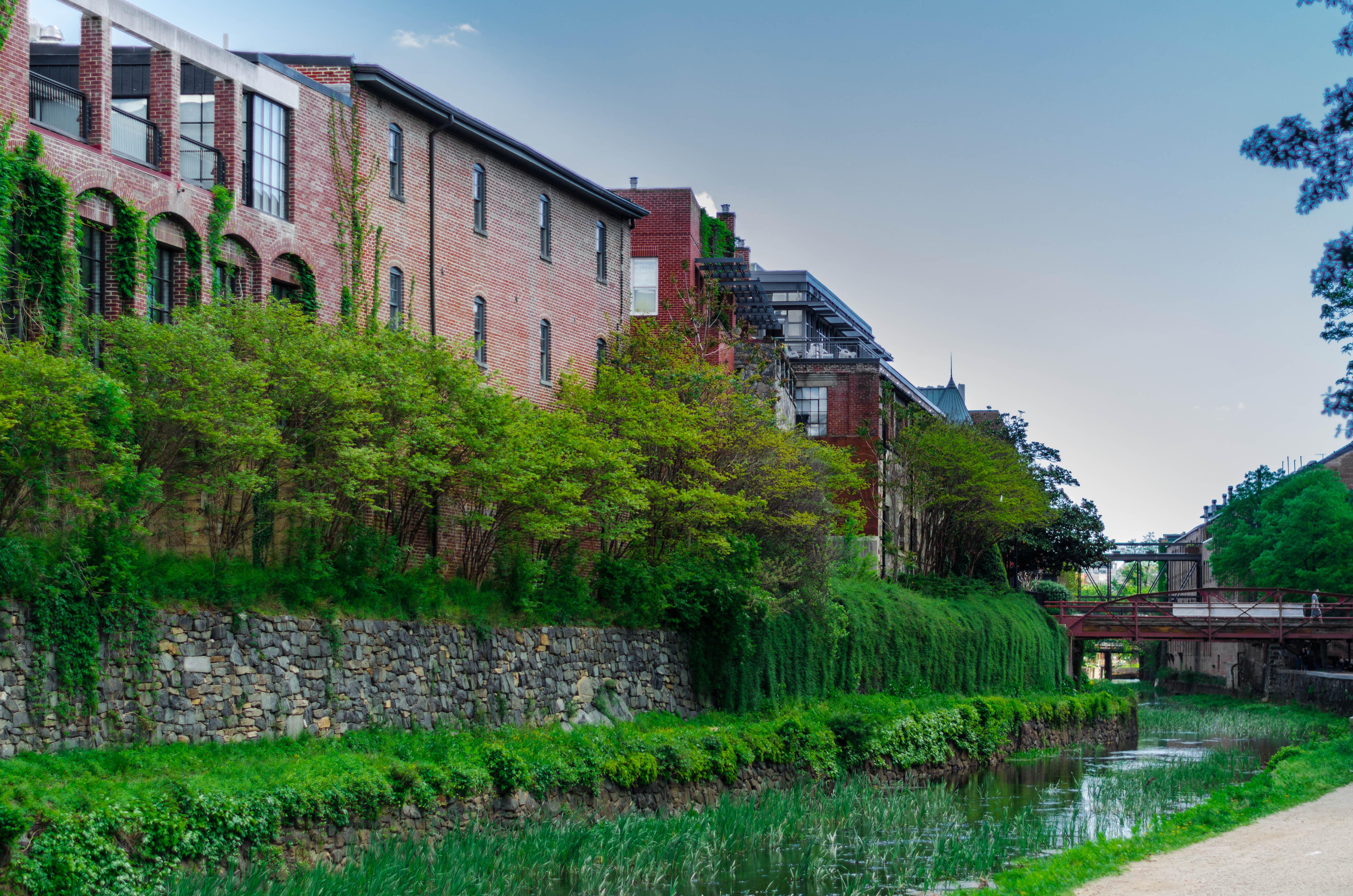 A canal along a walking path. Brick buildings line the ridges.