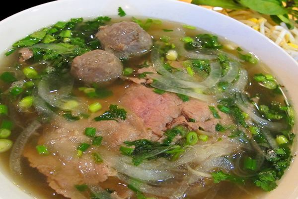 A close up of pho with rare beef, onions , herbs, and broth