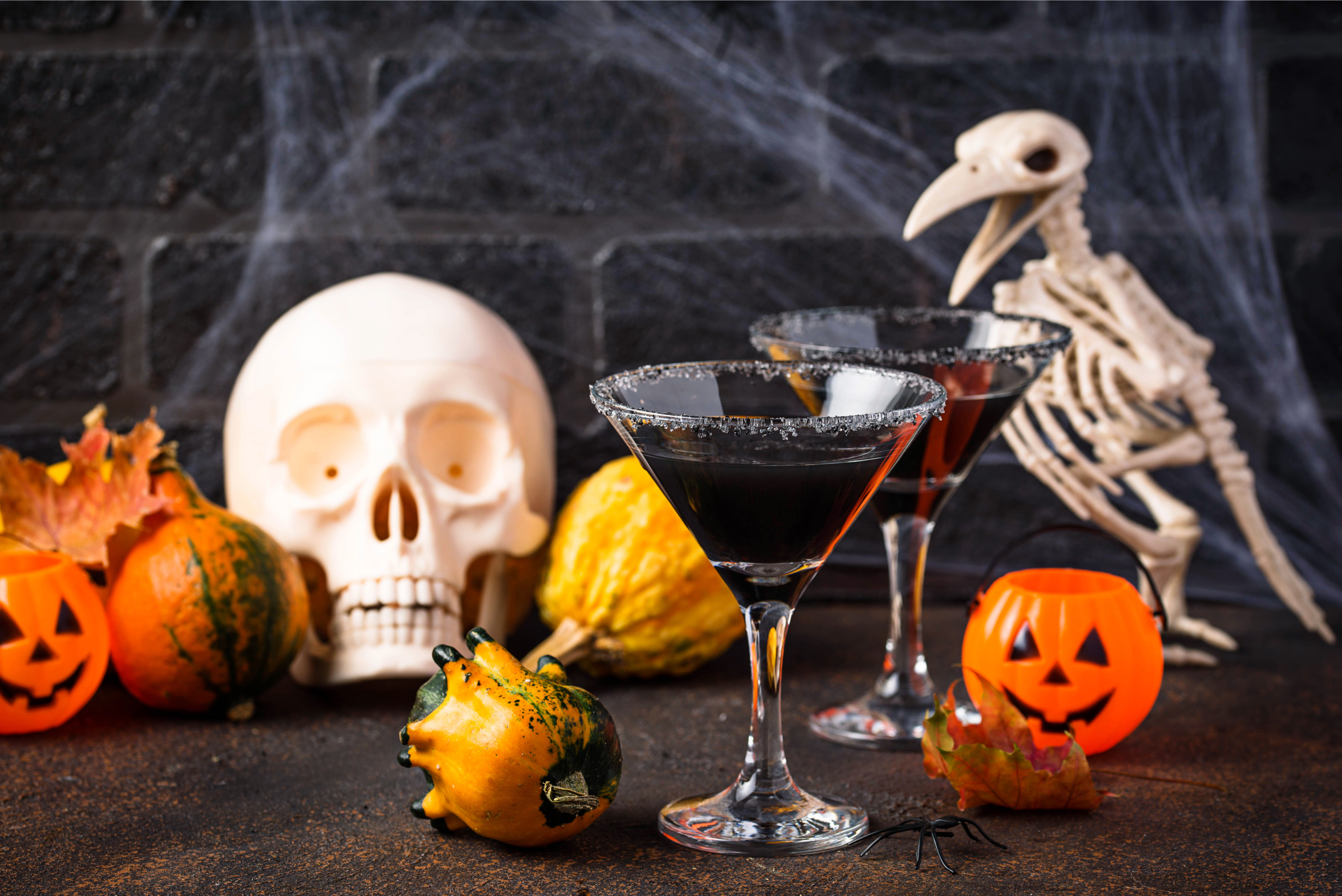 A Halloween display, with plastic jack o' lanterns, gourds, a bird skeleton, a skull, and two martini glasses filled with a dark liquid.