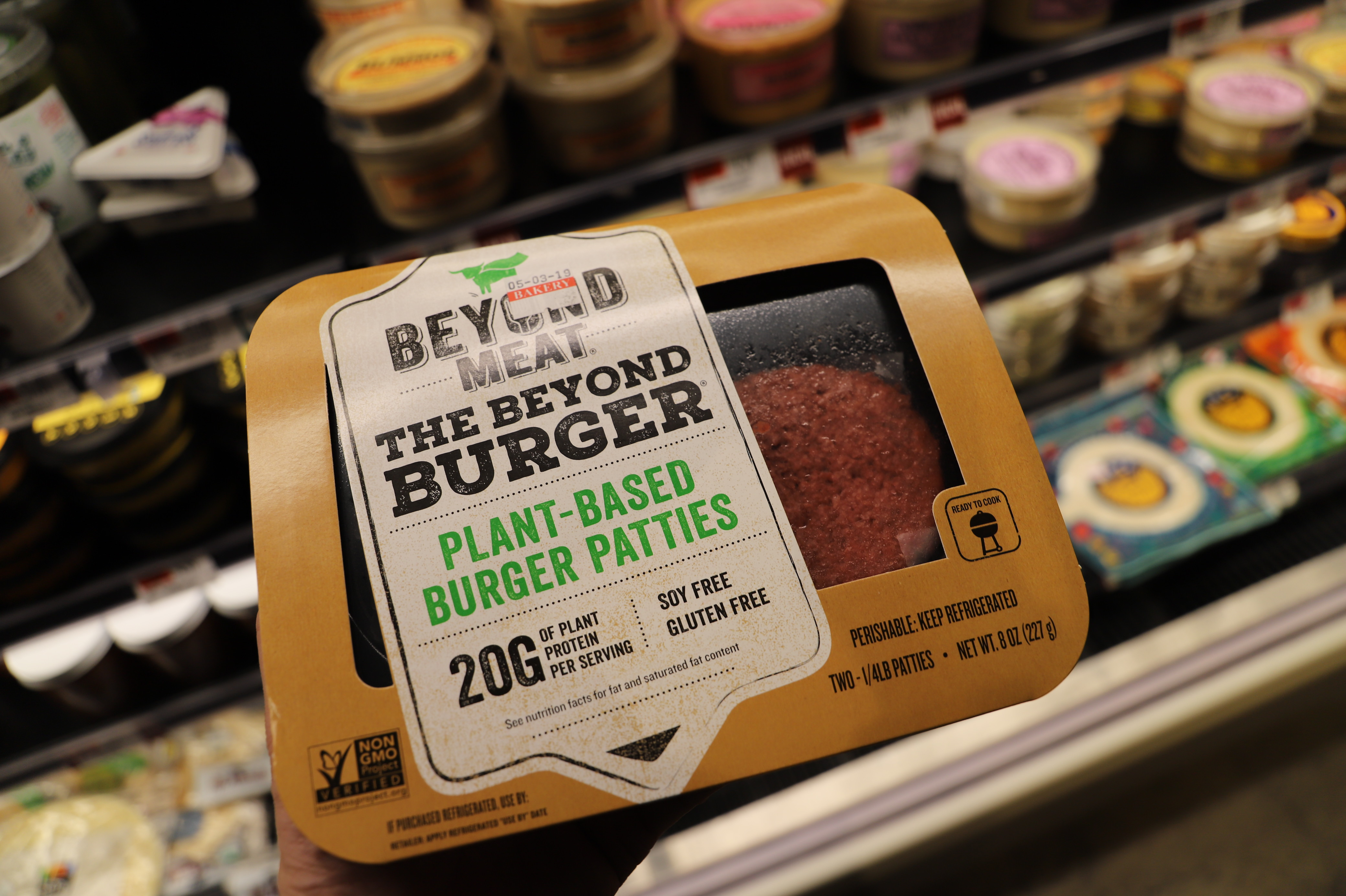 A Beyond Burger package held up in front of a grocery case.