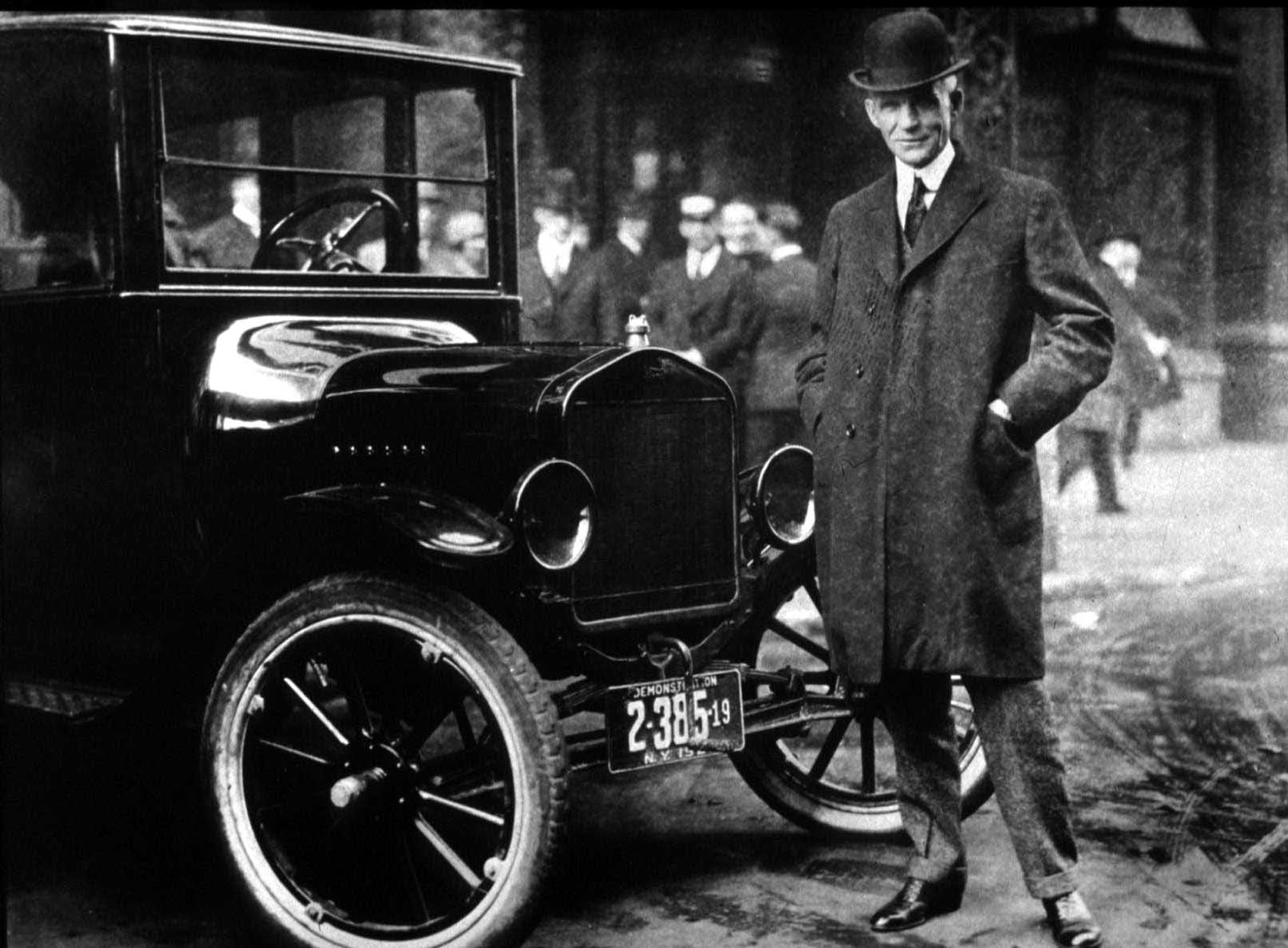 Henry Ford standing beside his Model T car.