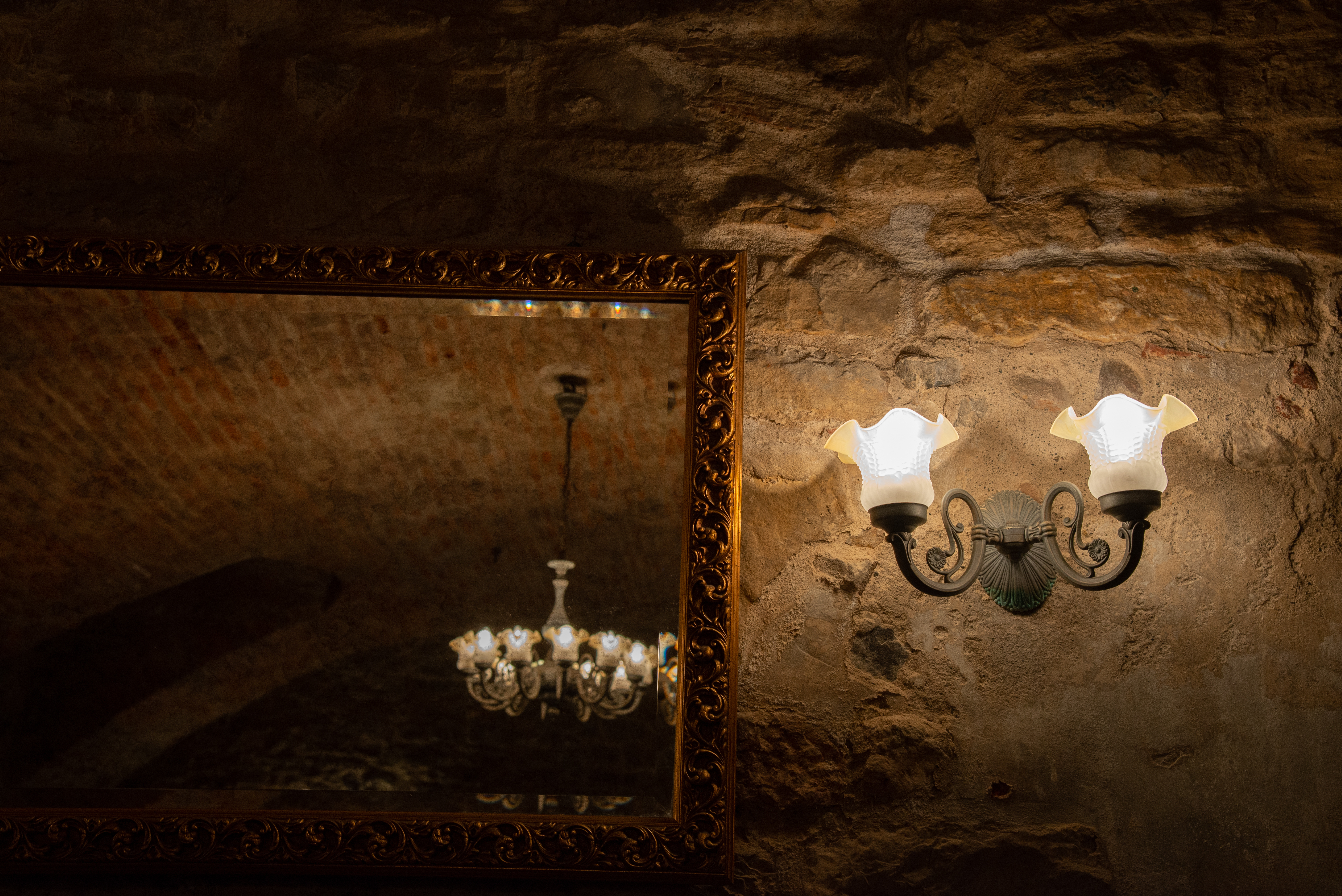 A gold mirror with an antique chandelier in the reflection and a two light antique sconce to the right