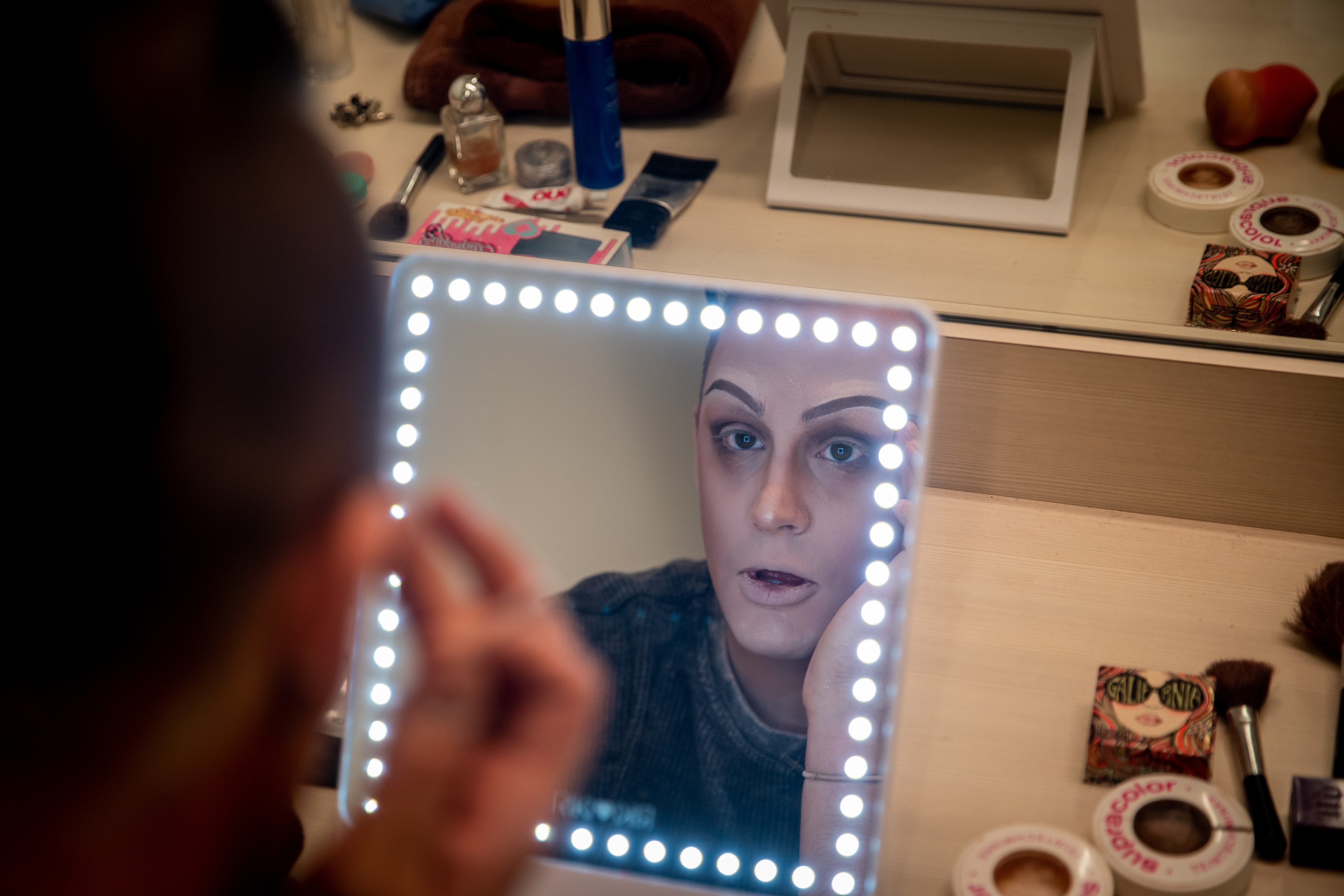 Claire Voyant about halfway through her drag makeup tutorial looking on her mirror.