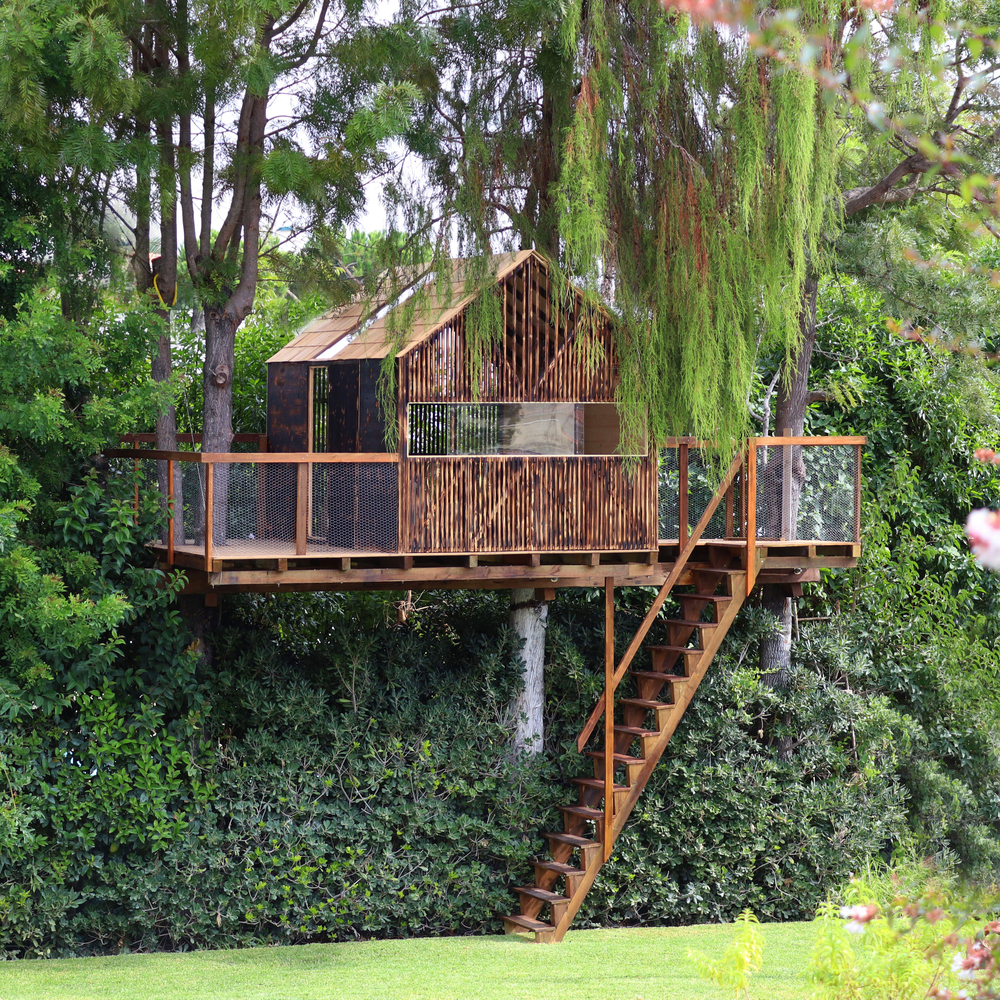 Wooden pitch-roofed treehouse in a backyard.