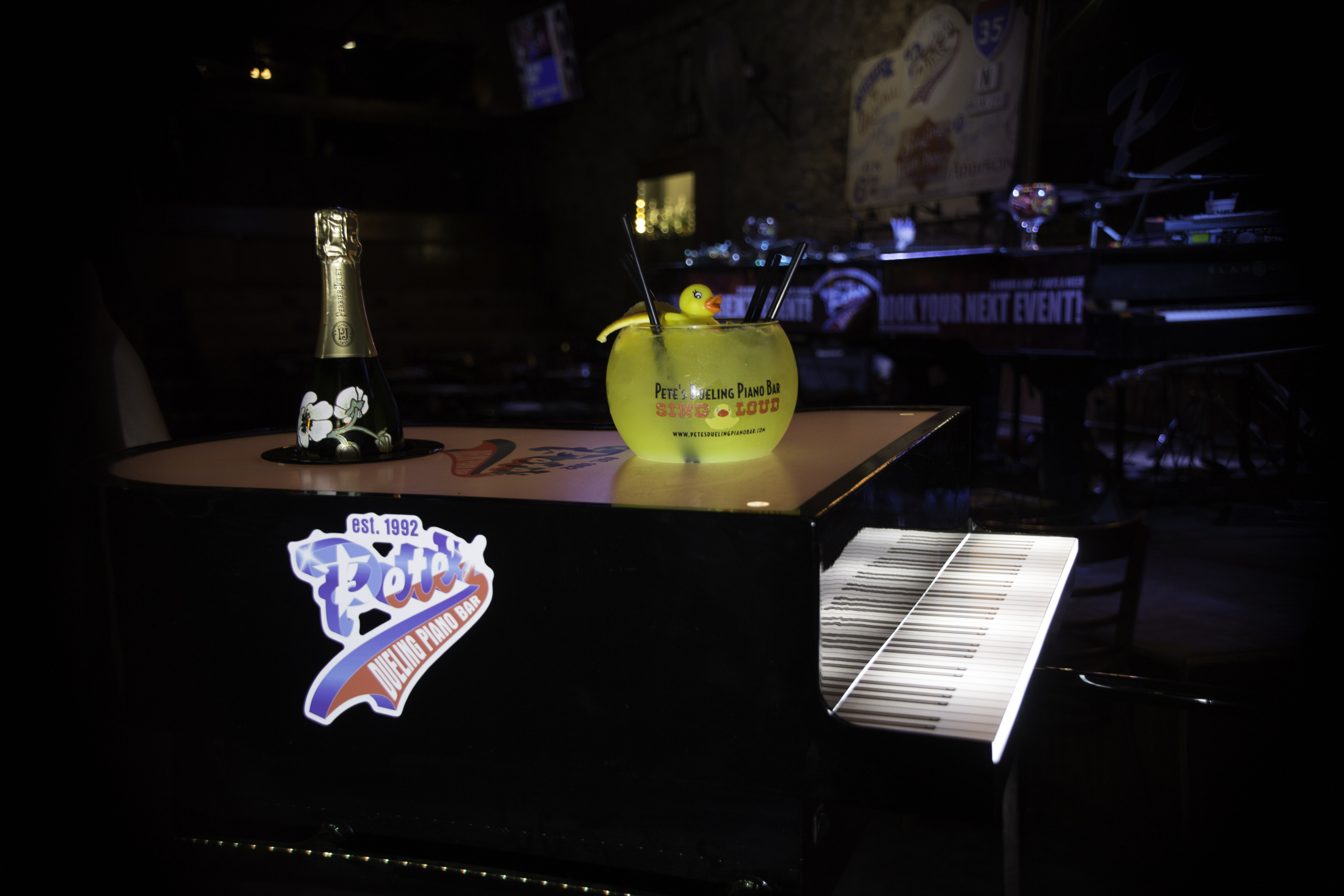 An oversized yellow cocktail sits on a piano with the Pete's logo.