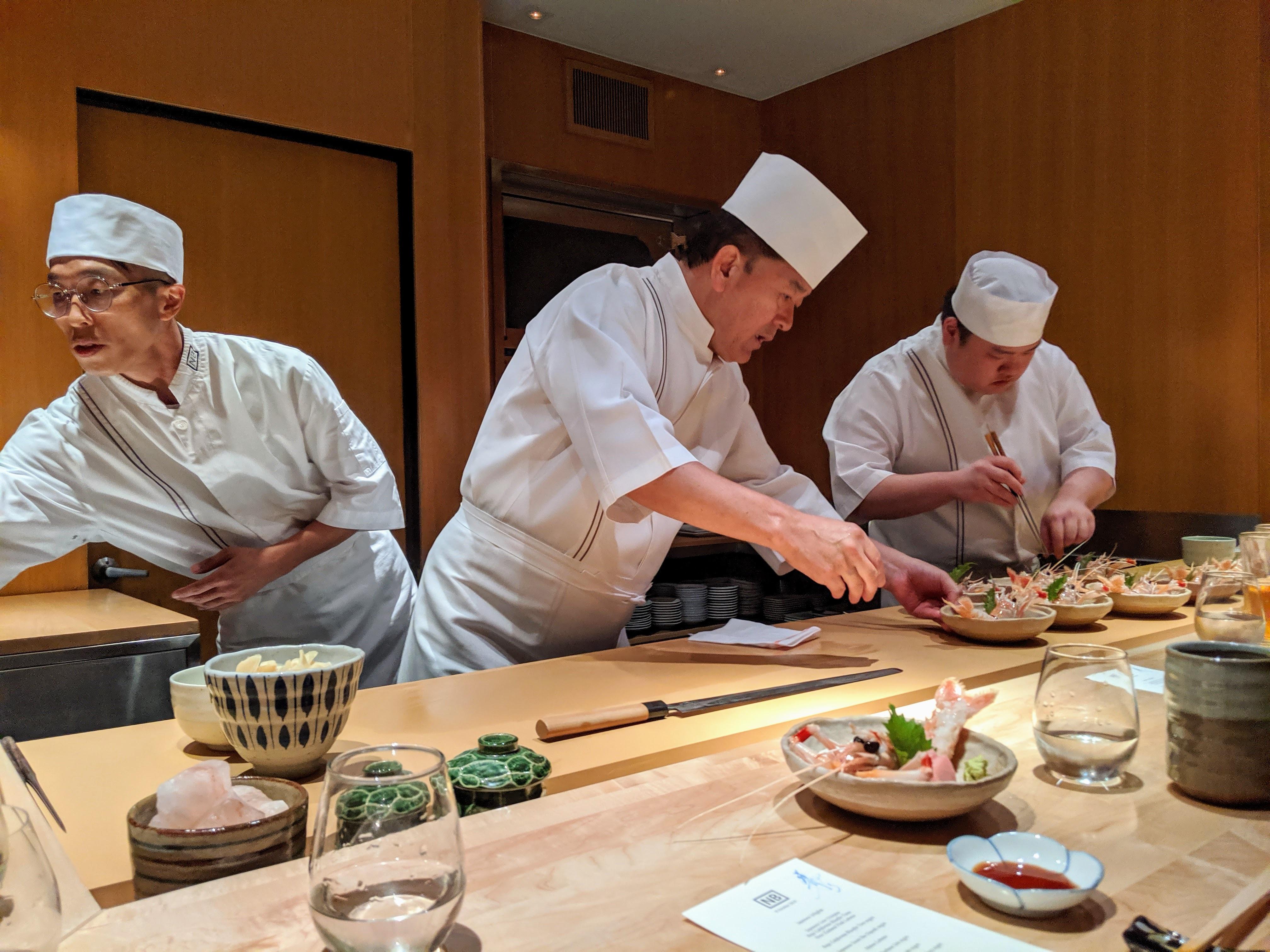 Chef Osamu Fujita of Nozawa Bar working with other chefs at the counter.
