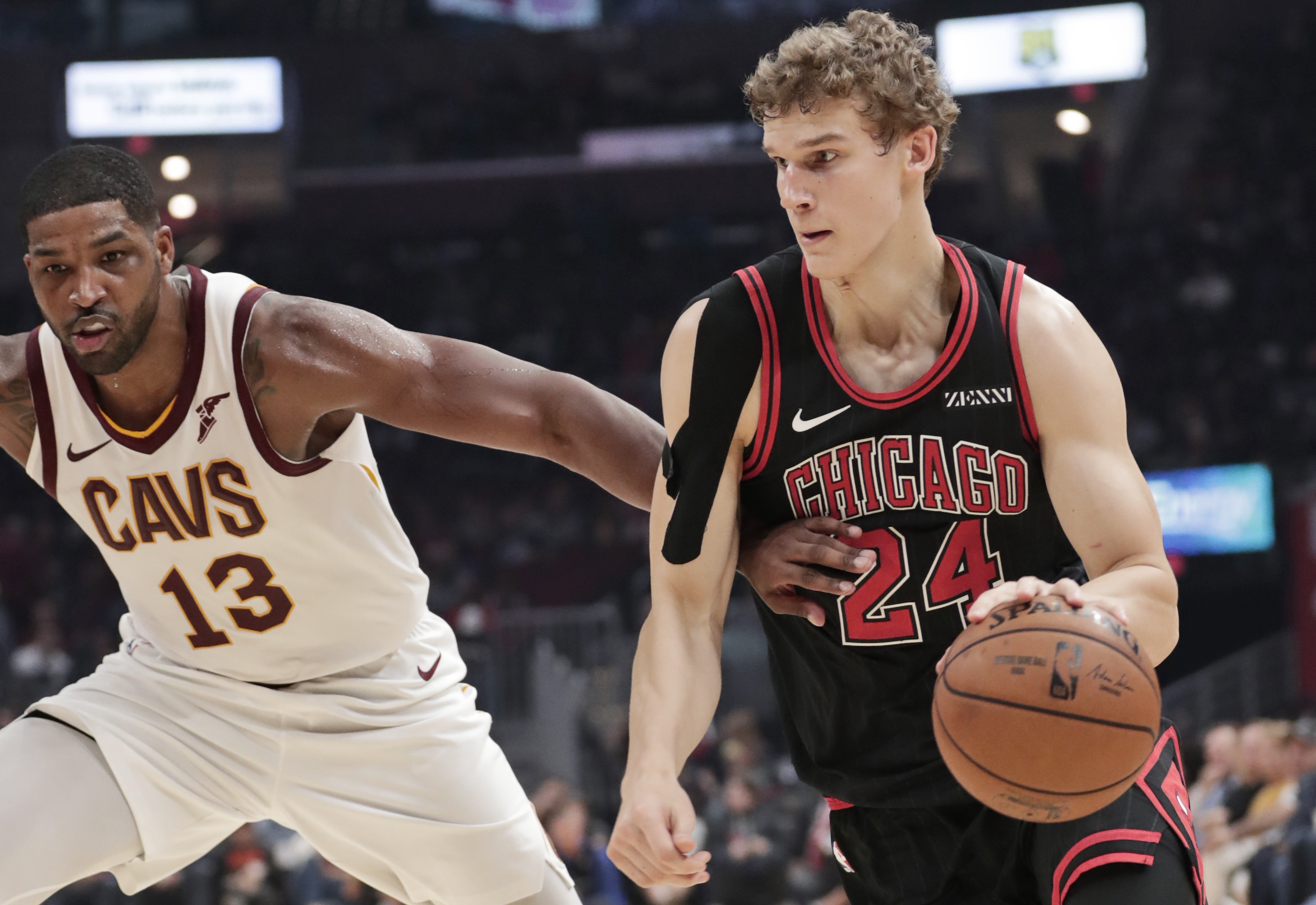The Bulls' Lauri Markkanen drives around the Cavaliers' Tristan Thompson Wednesday night in Cleveland.