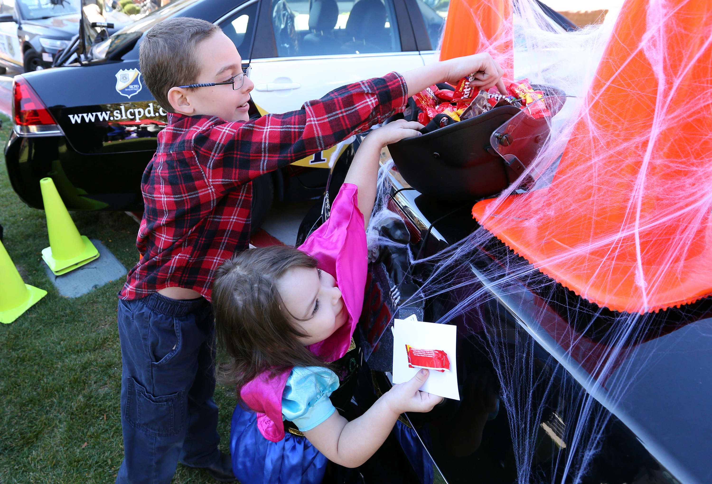 Jayden Hart and Nicole Hart reach for candy from the Salt Lake City police department's Trunk or Treat at the Utah Foster Care Pumpkin Festival at The Gateway in Salt Lake City on Friday, Oct. 21, 2016.
