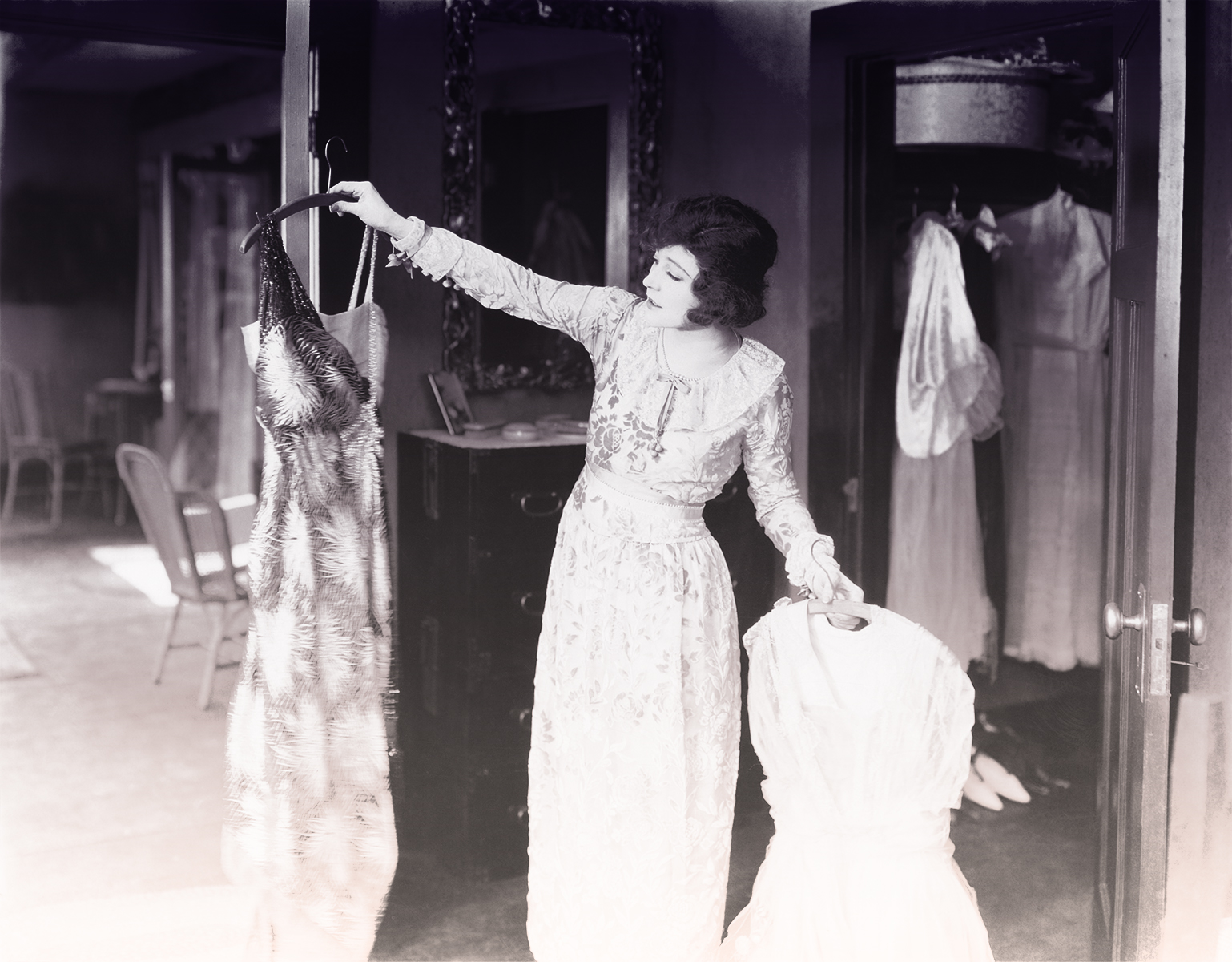 A woman from the 1920s holds up a hanger with a dress and looks at it while holding a white dress in her other hand.