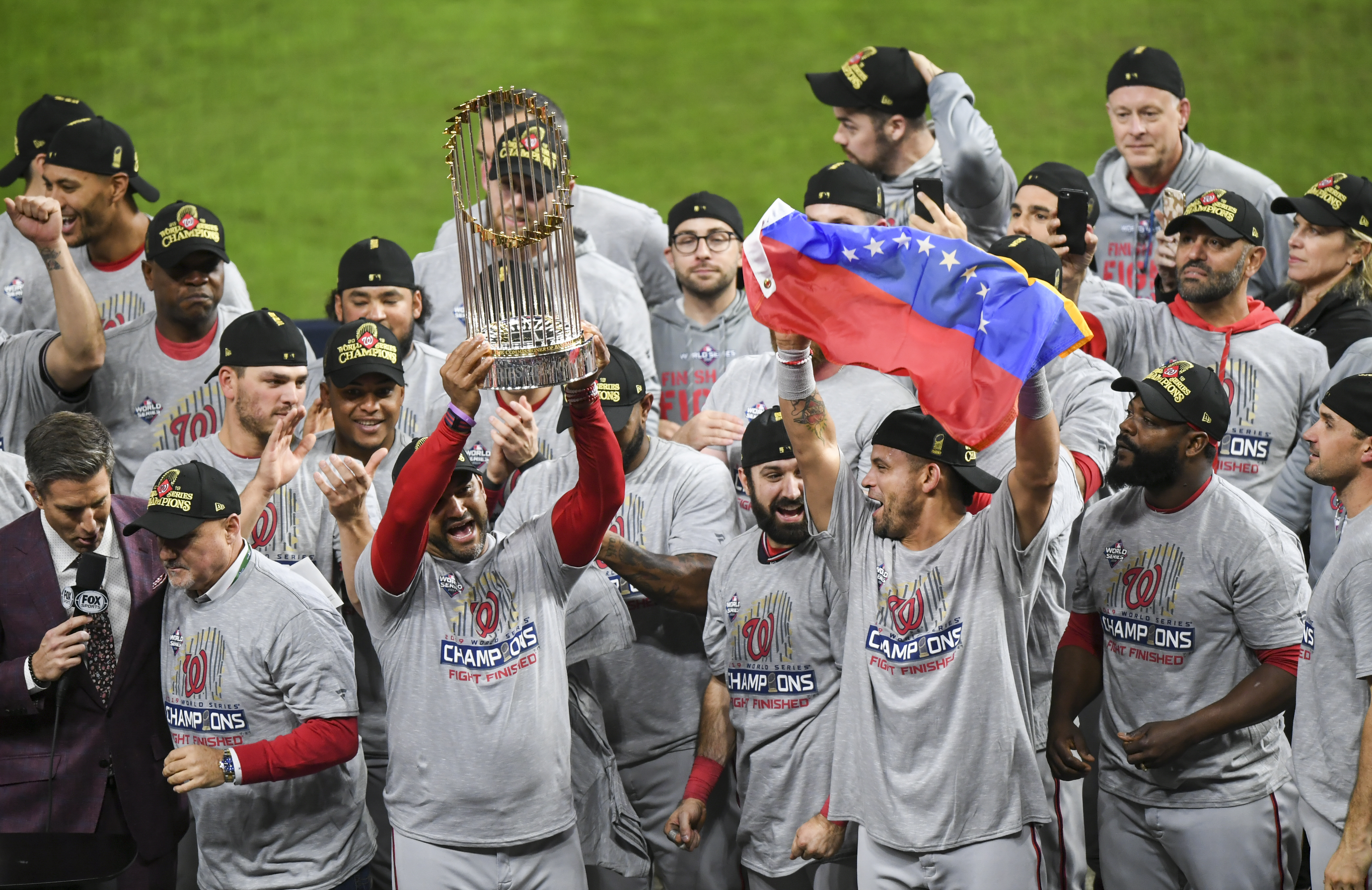 A baseball team gathers on a baseball field after winning a championship match. One of the players holds a trophy while another holds a flag.