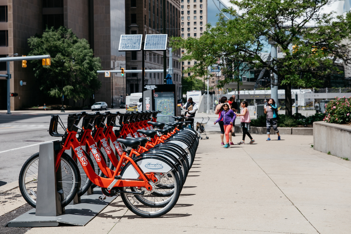 A row of red frame bikes locked at in a metal station on a downtown sidewalk.