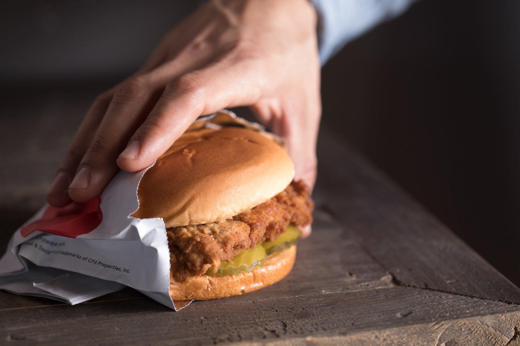 A hand grabbing a chicken sandwich
