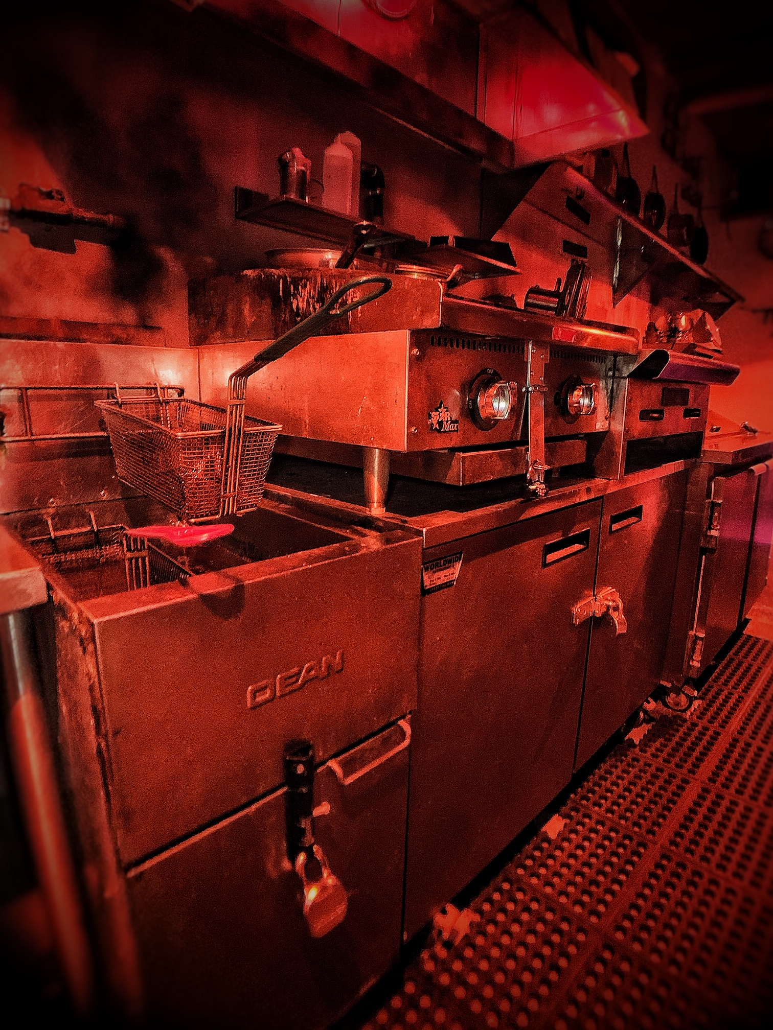 A red-tinted photo of a grimy, derelict-looking restaurant kitchen.