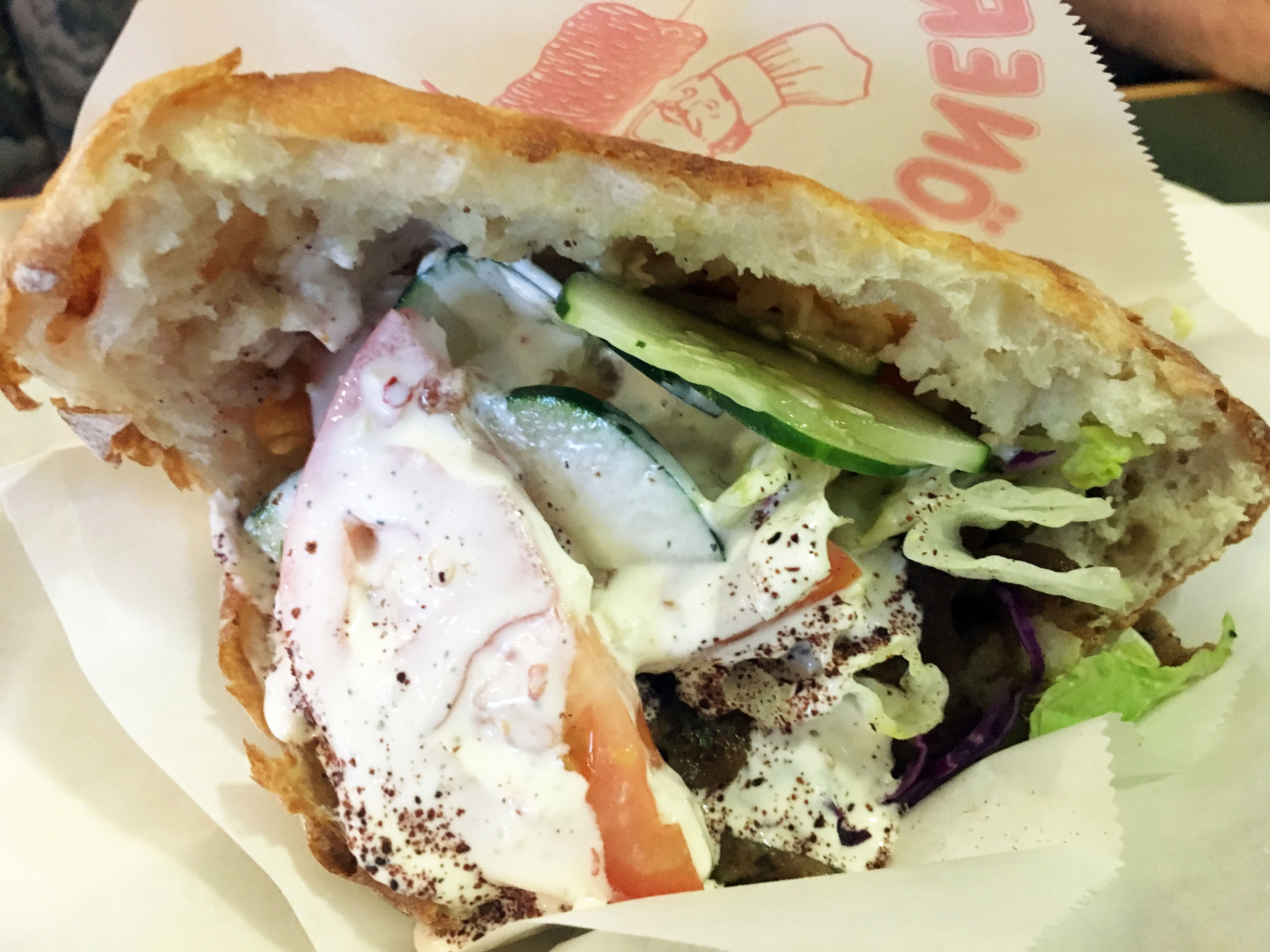 A close up of a döner sandwich with veggies and meat stuffed in a pocket of soft white bread and drenched with creamy white sauce.