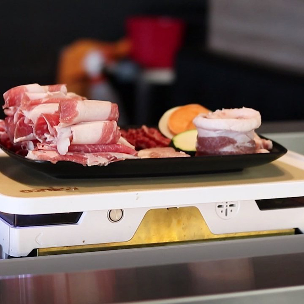 An automated train delivers meats and vegetables at Master Kim's Korean BBQ.