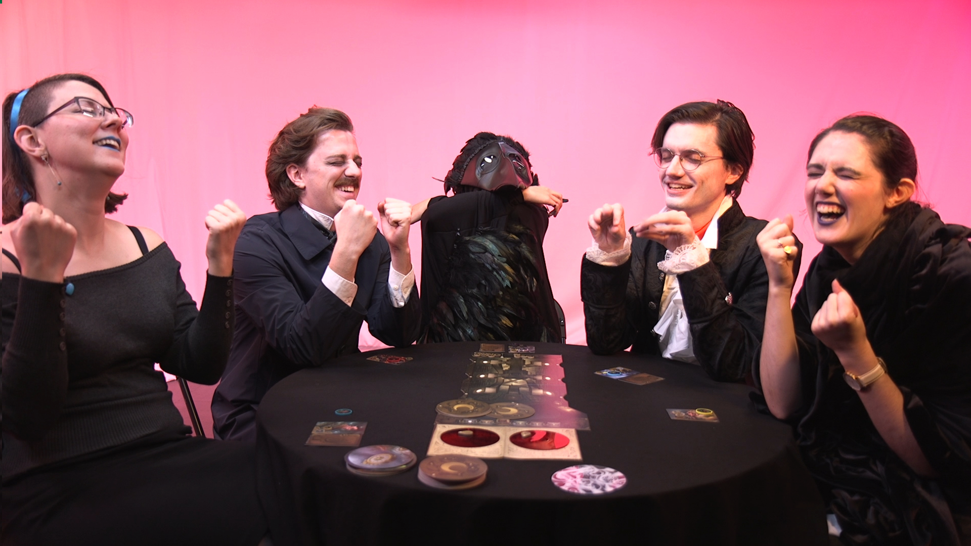 A group of people sitting around a board game with their eyes closed, hands held up, and laughing boisterously