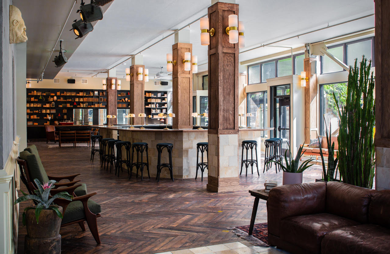 A picture of the wooden floors, rustic unfinished stone bar, and bookshelves of Vivian